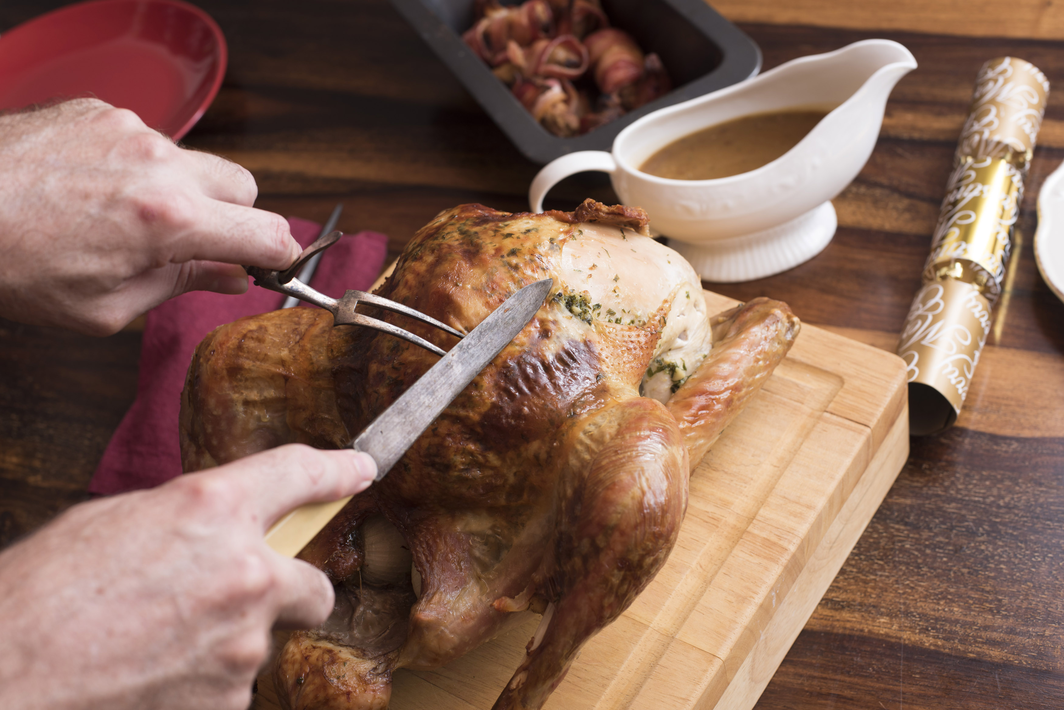Man carving a Christmas turkey with vintage bone handled utensils on a wooden cutting board on a decorated table with gravy in a sauce boat