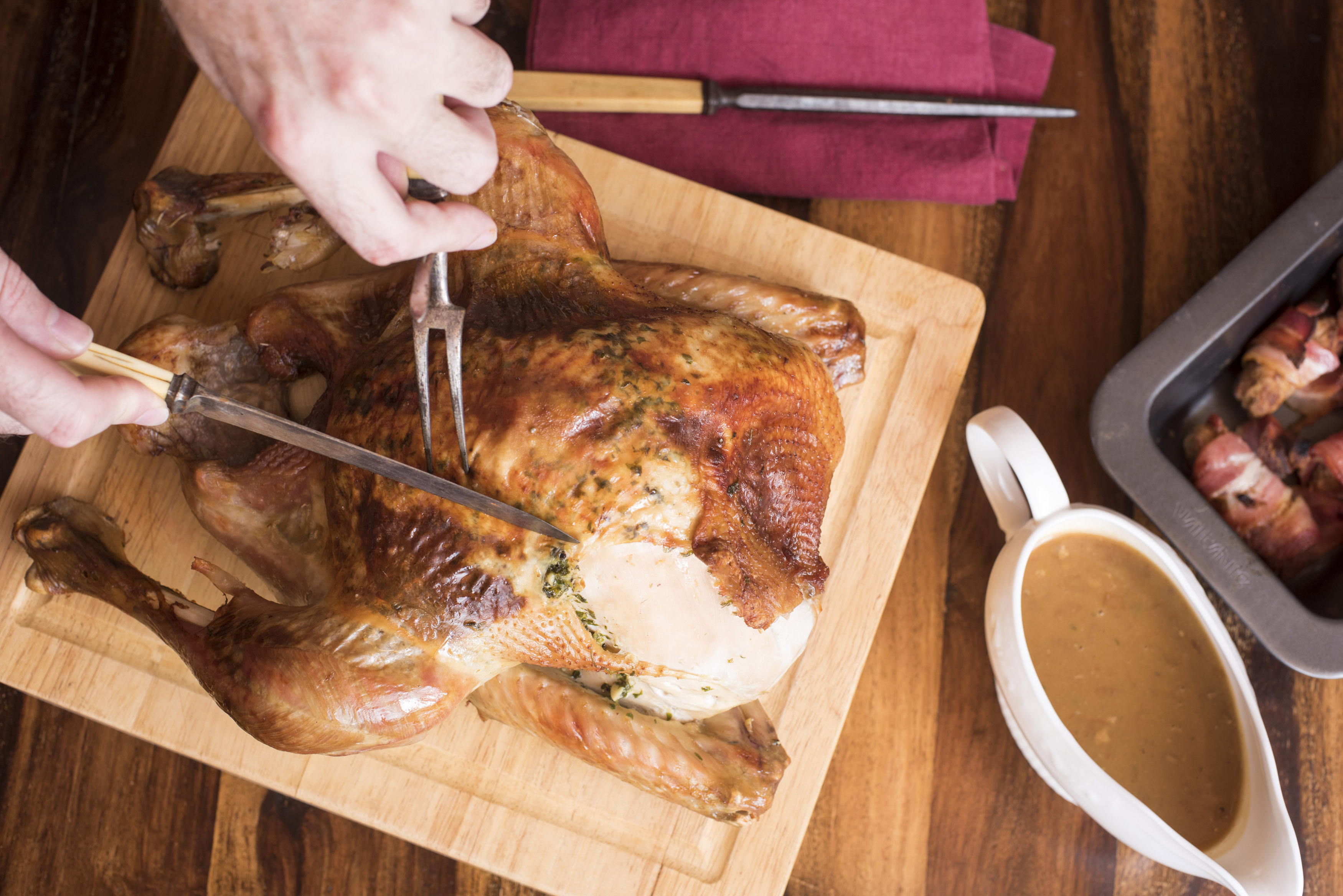 Person carving roasted thanksgiving turkey on wooden board