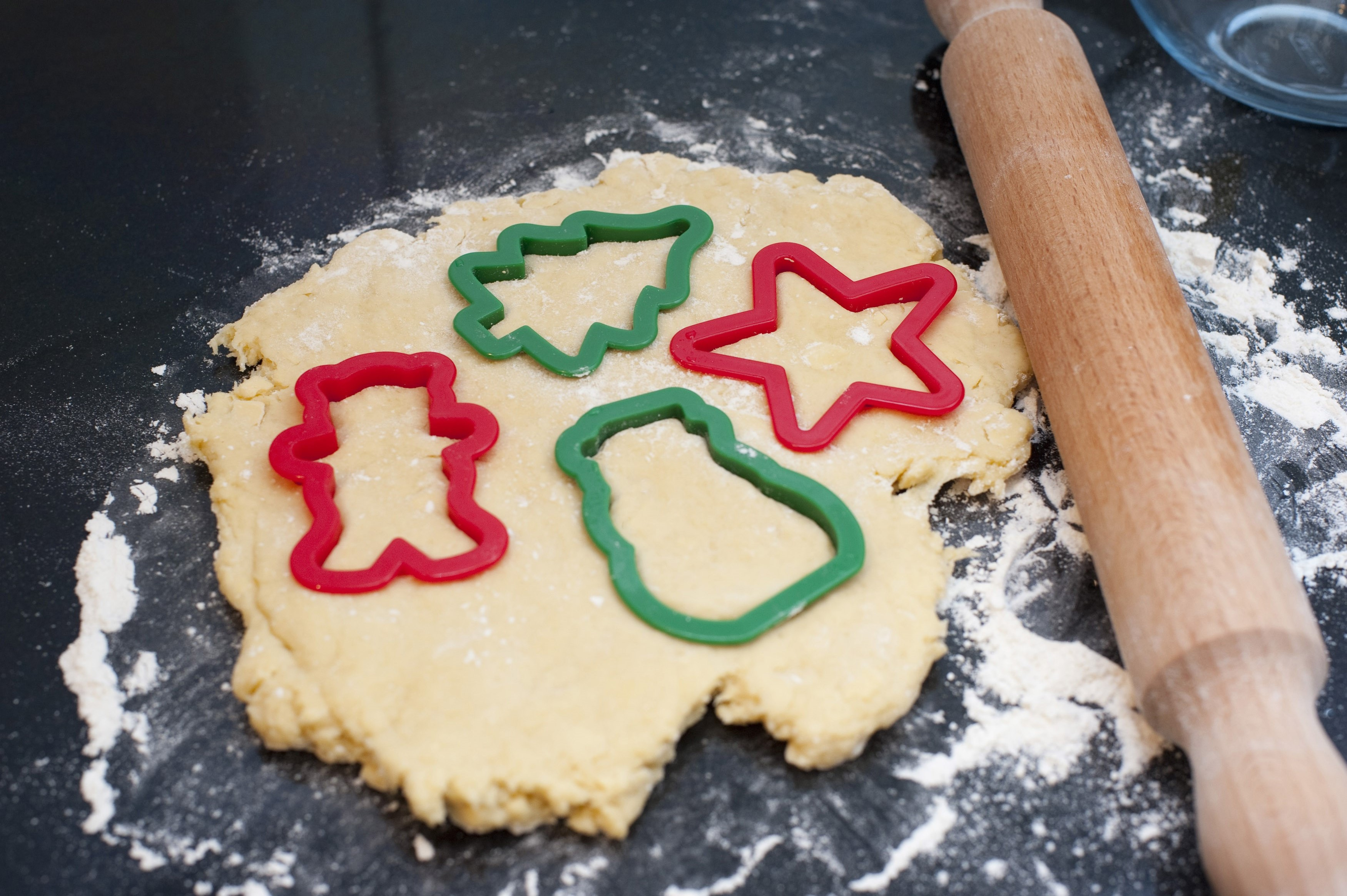 Rolled pastry dough with cookie cutters in traditional Christmas shapes for making seasonal cookies and biscuits