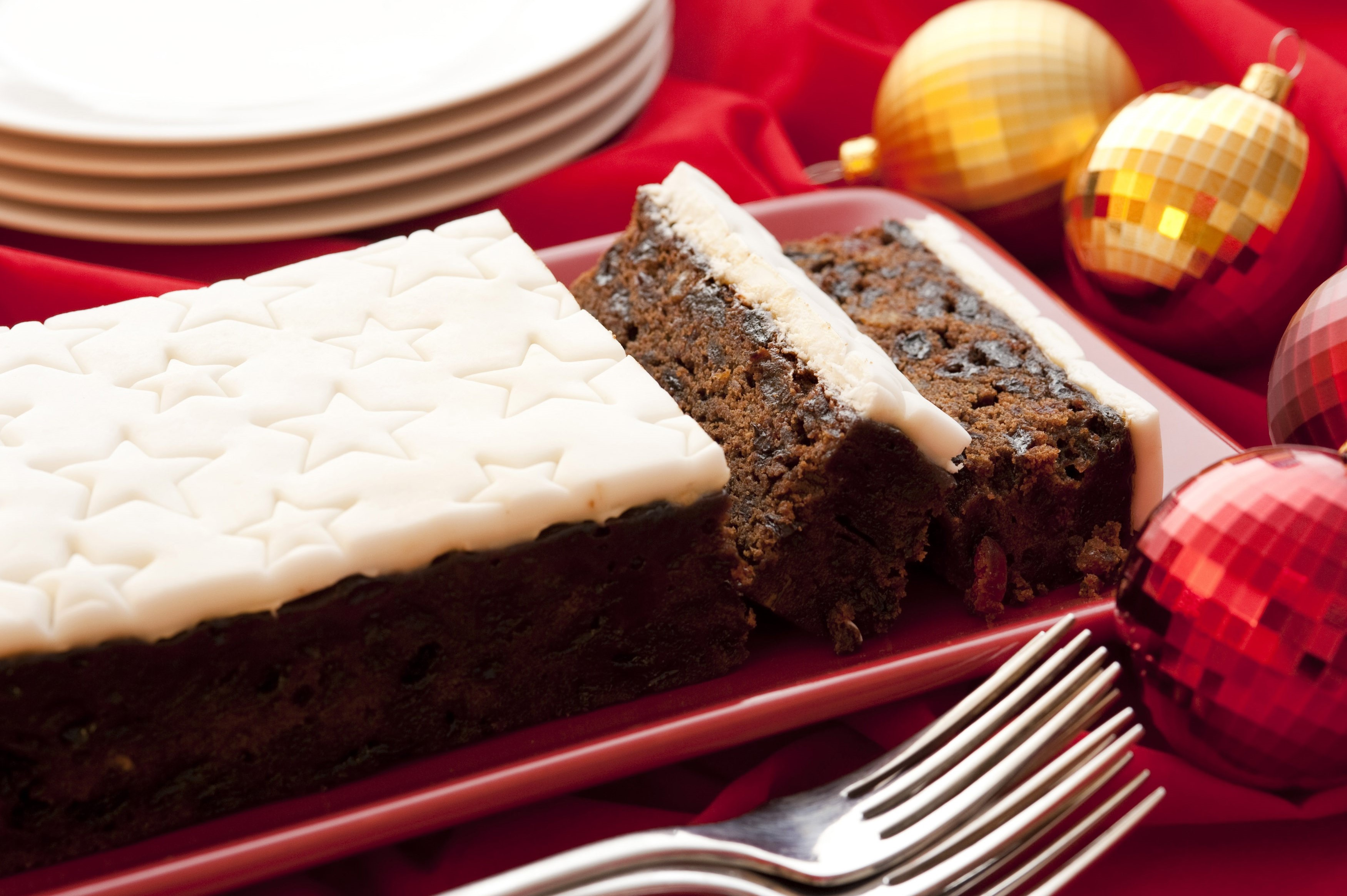 Traditional fruity Christmas cake with decorative star icing sliced and served on a platter on a festive Christmas table with ornaments