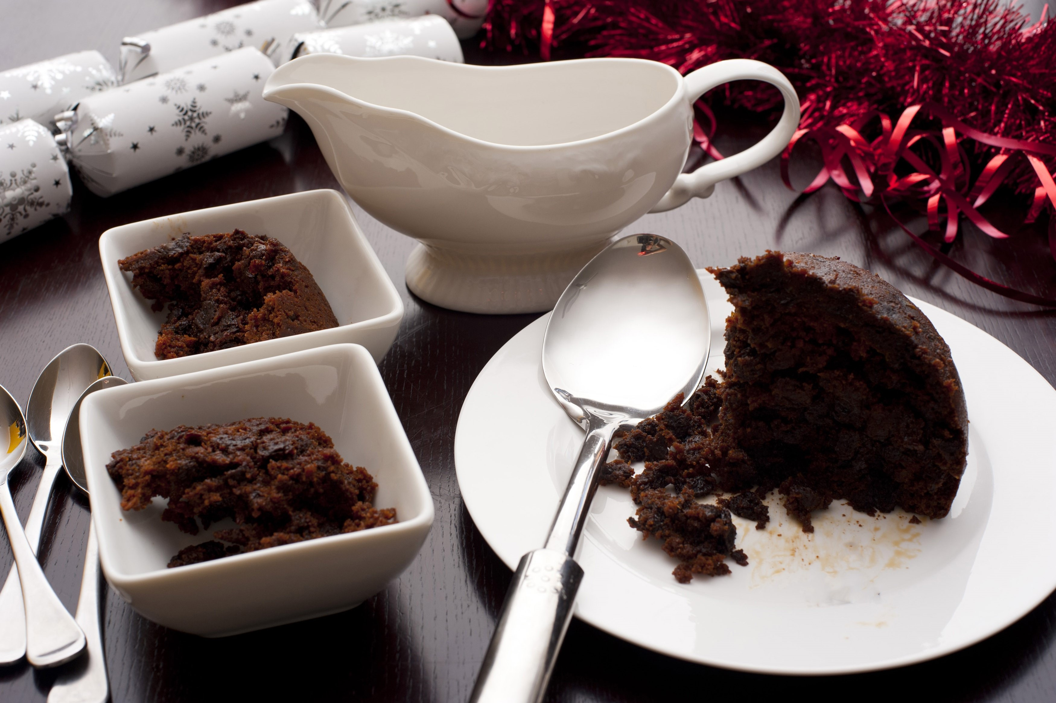 Servings of delicious rich spiced fruity Christmas pudding in bowls on a seasonal festive Xmas table