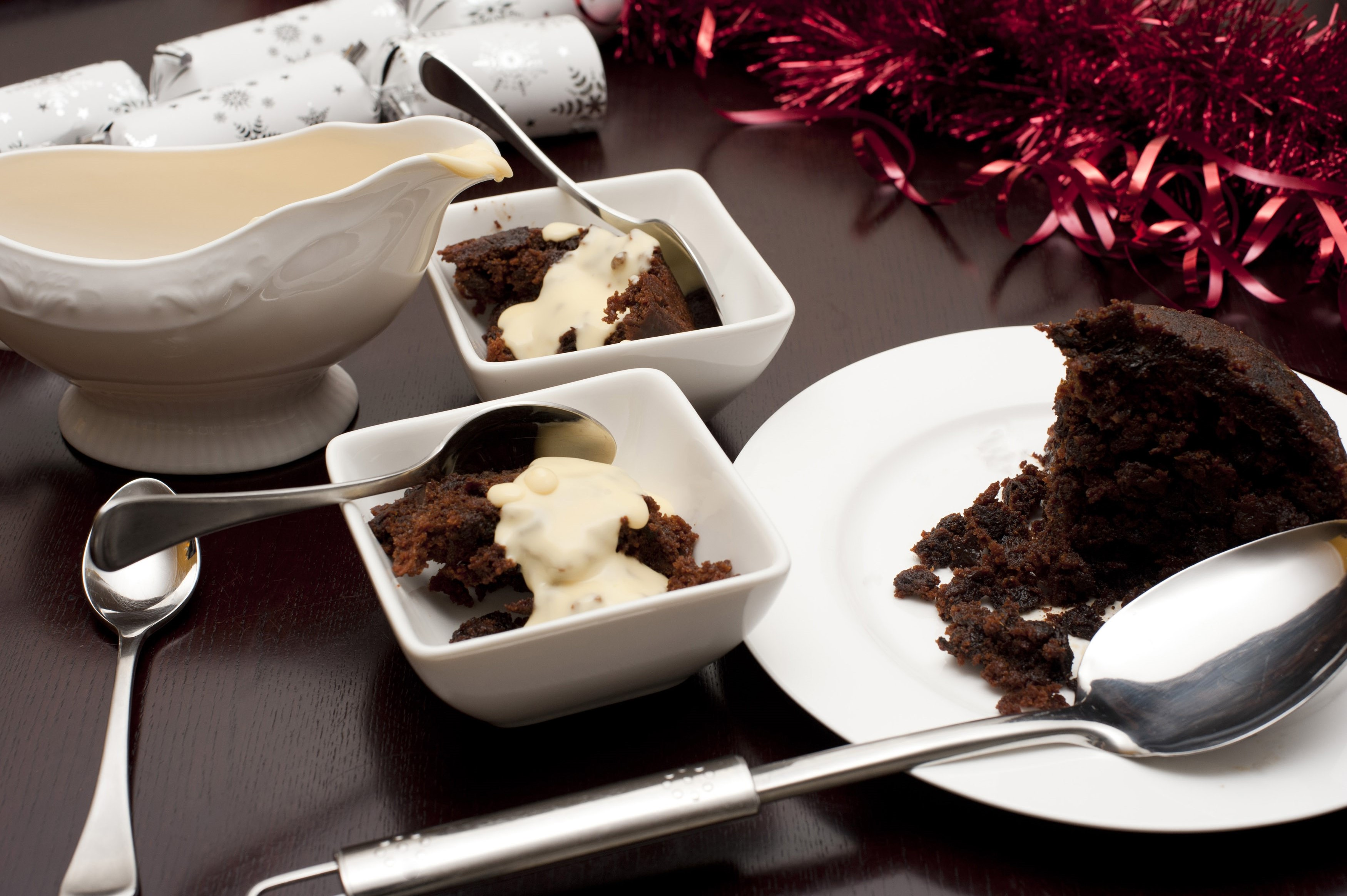 Traditional steamed fruity Christmas pudding served with rich brandy cream on a Christmas table
