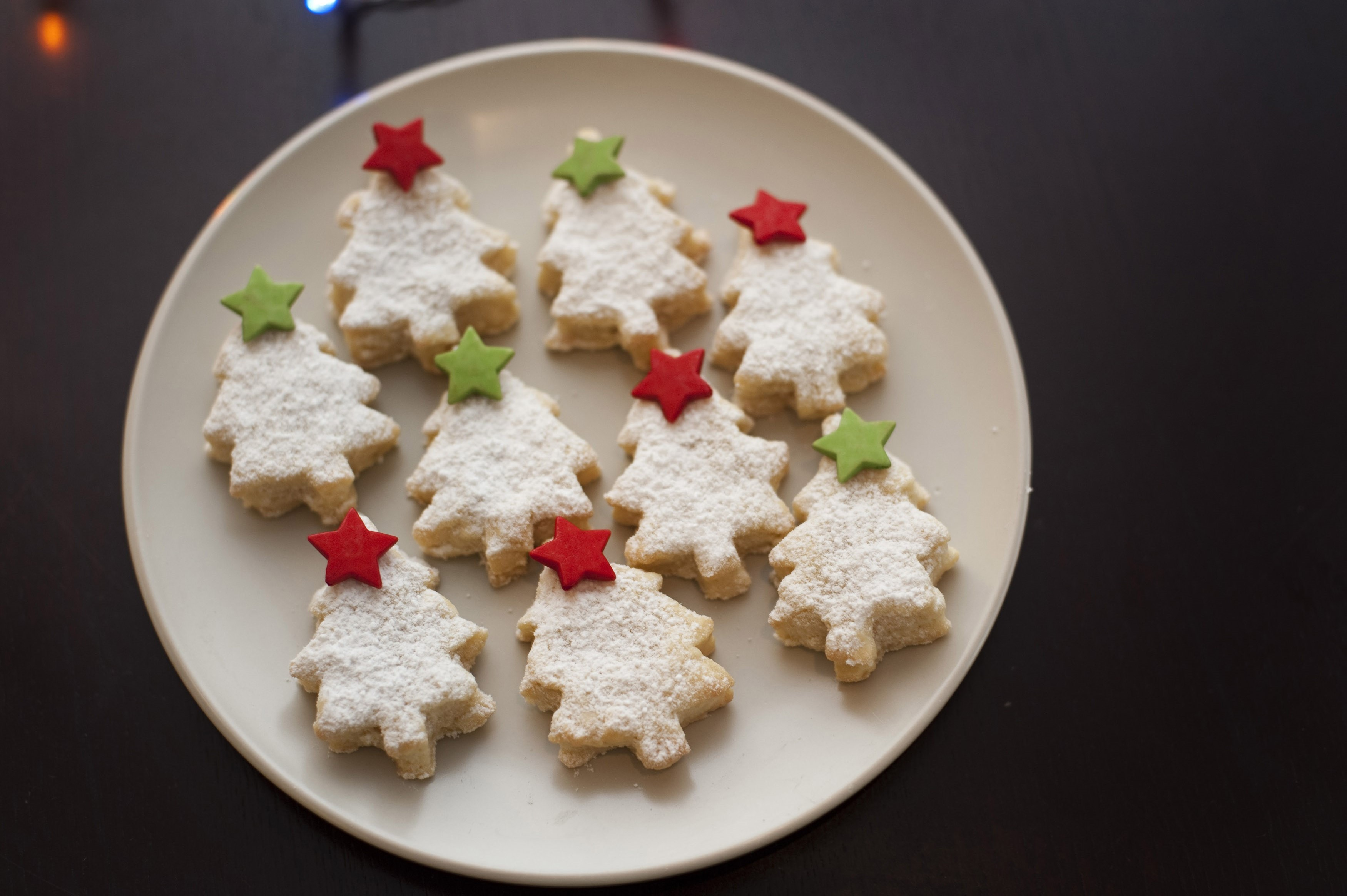 Plate of freshly baked homemade Christmas tree cookies decorated with colourful stars in green and red, high angle view