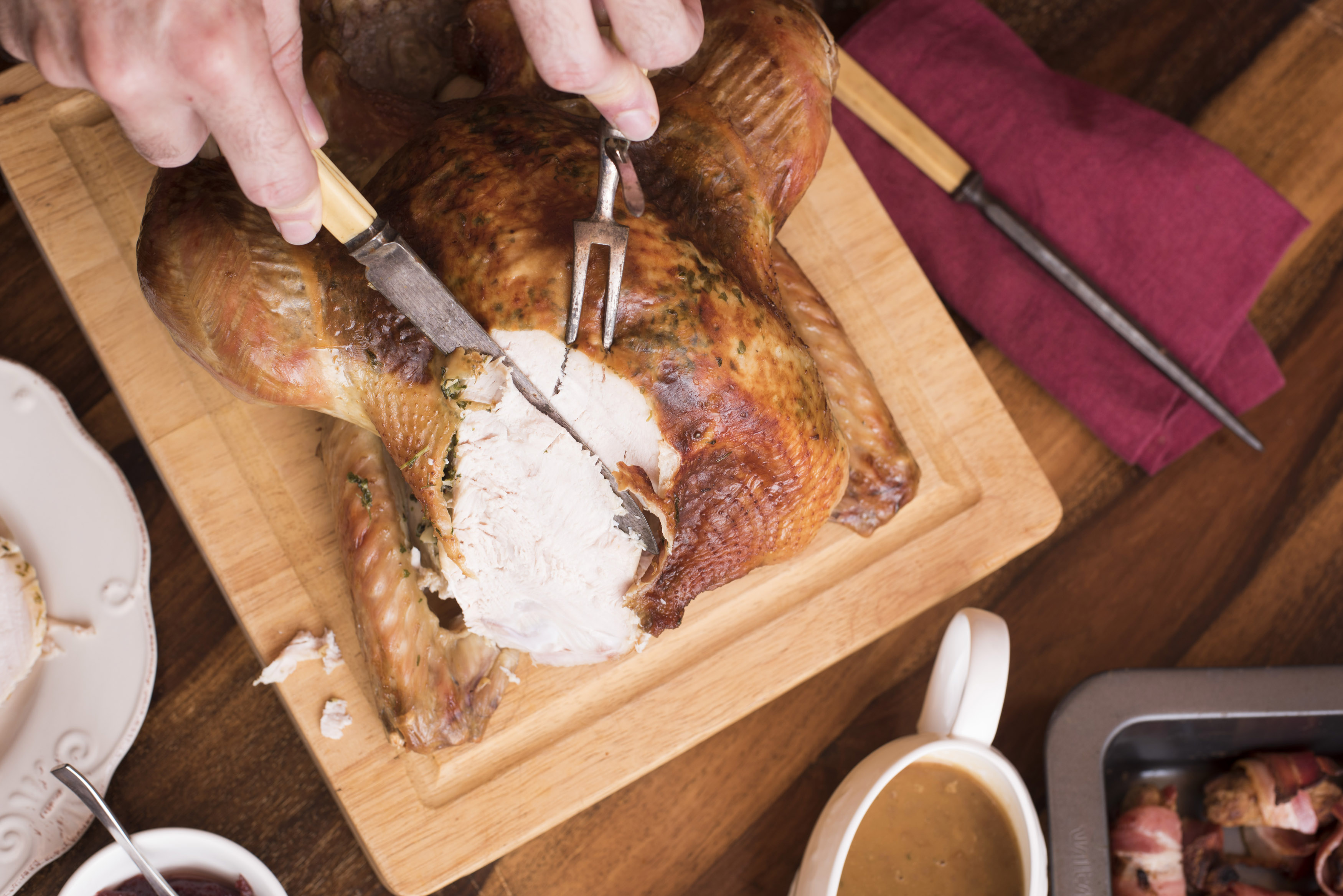 Man carving the breast of a Christmas turkey with vintage utensils in a cropped overhead view on the table