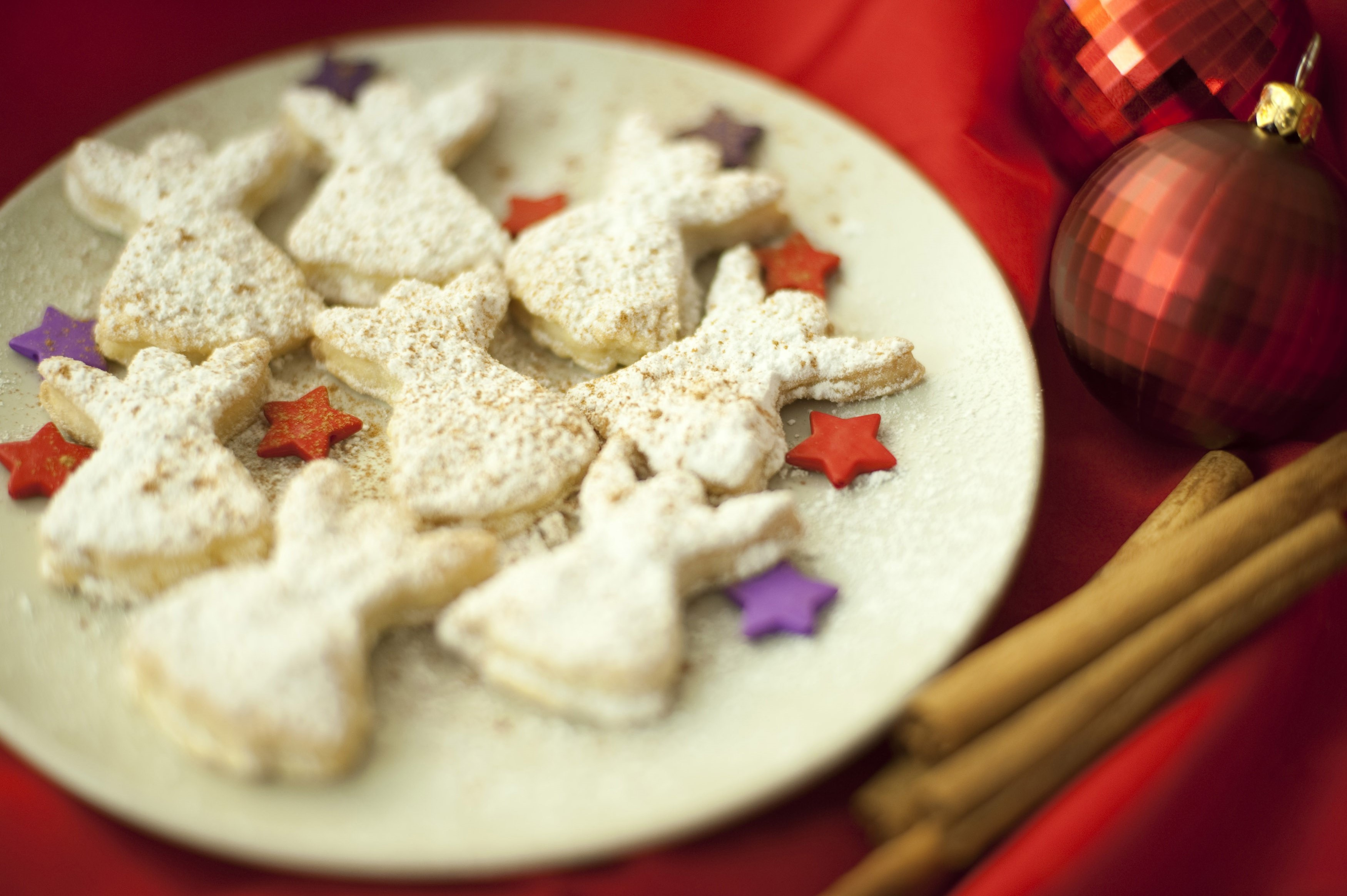 Plate of traditional freshly baked homemade golden Angel Christmas cookies interspersed with colourful stars on a Christmas table