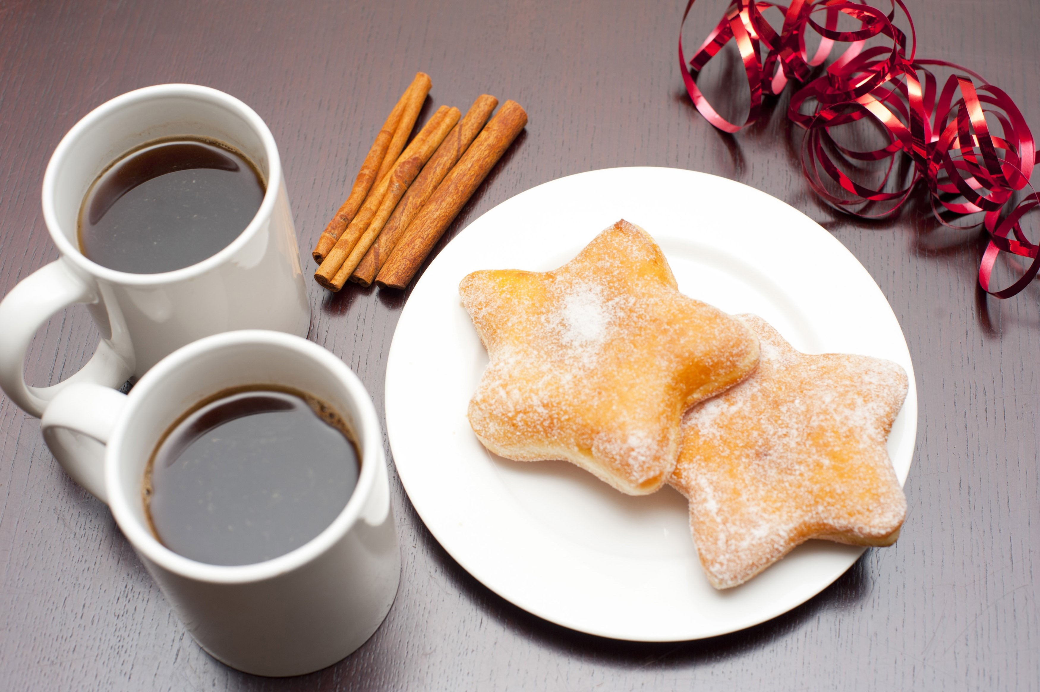 High angle view of two mugs of black espresso coffee served with Christmas doughnuts in a traditional star shape