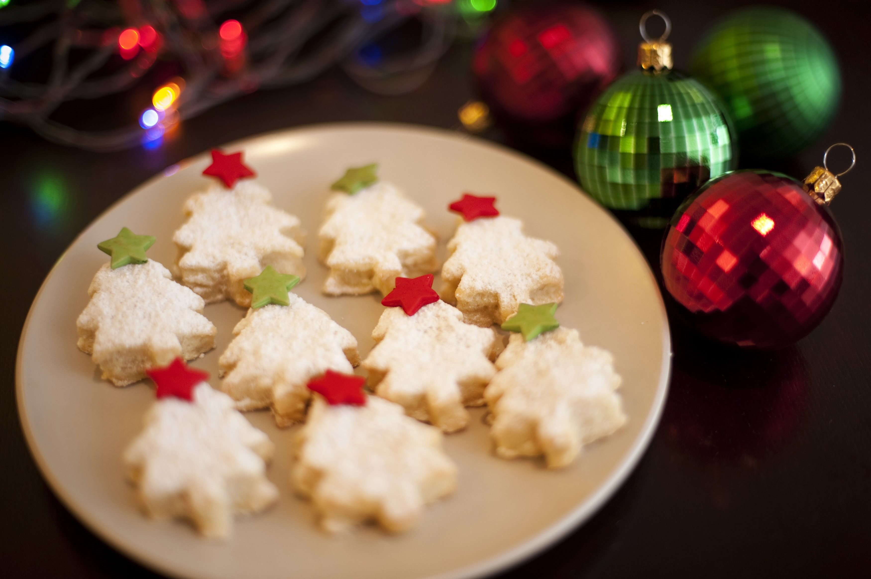 Golden freshly baked Christmas cookies in the form of Christmas trees decorated with colourful, red and green stars served on a plate, high angle view with Xmas ornaments
