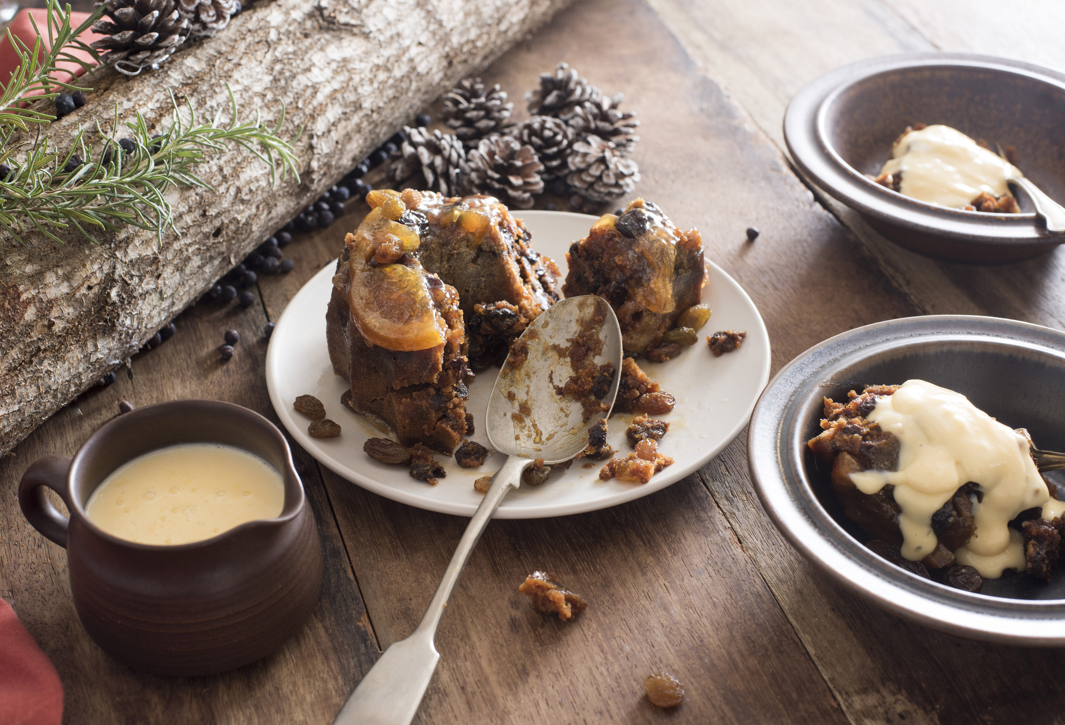 Christmas pudding served in two bowls topped with brandy sauce on a wooden table with the remnants of the dessert on a plate in the center