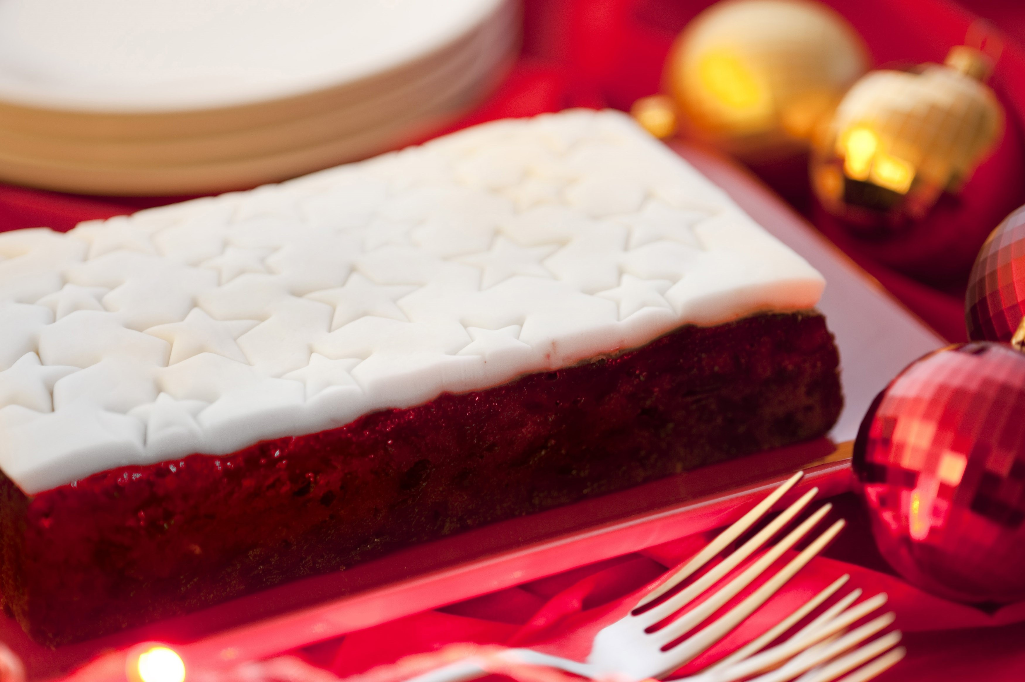 Traditional Christmas fruit cake with decorative white icing with stars served on a Christmas table with colourful baubles