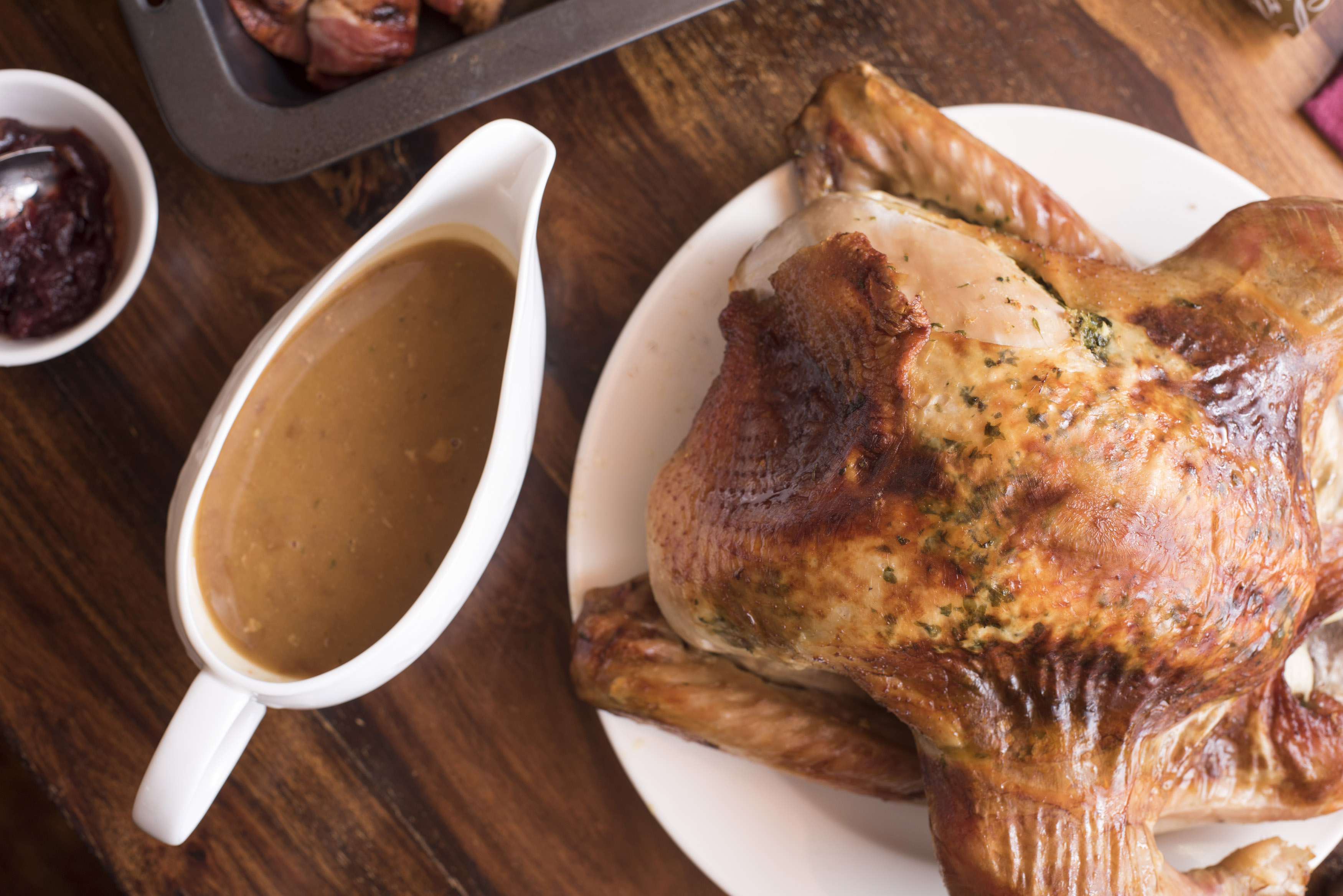 Roast Christmas or Thanksgiving turkey and gravy served on a table ready to be carved for a festive holiday celebration