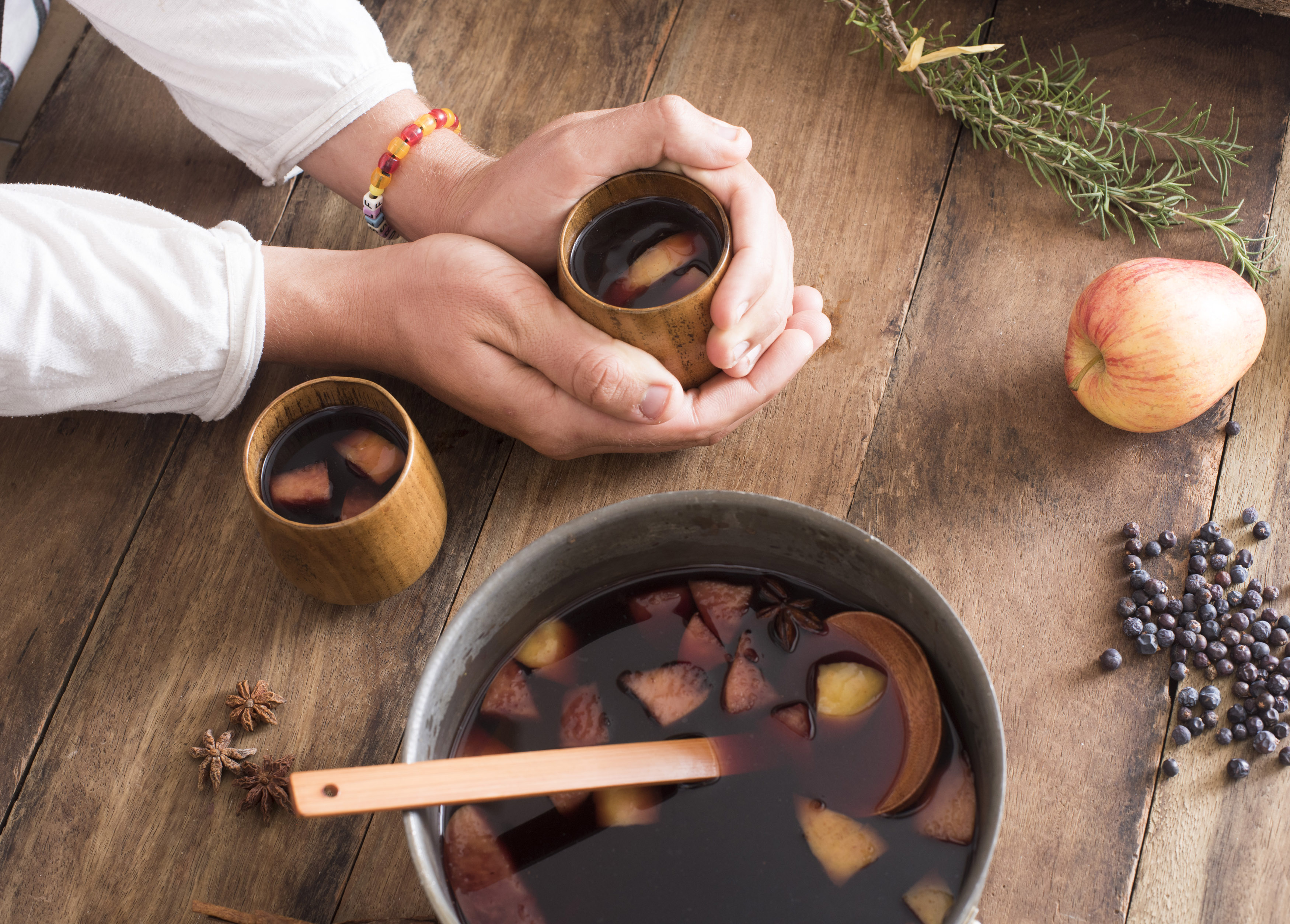 Person making mulled red wine in a bowl with fruit, herbs and spices with ingredients and two full mugs to celebrate the holiday season