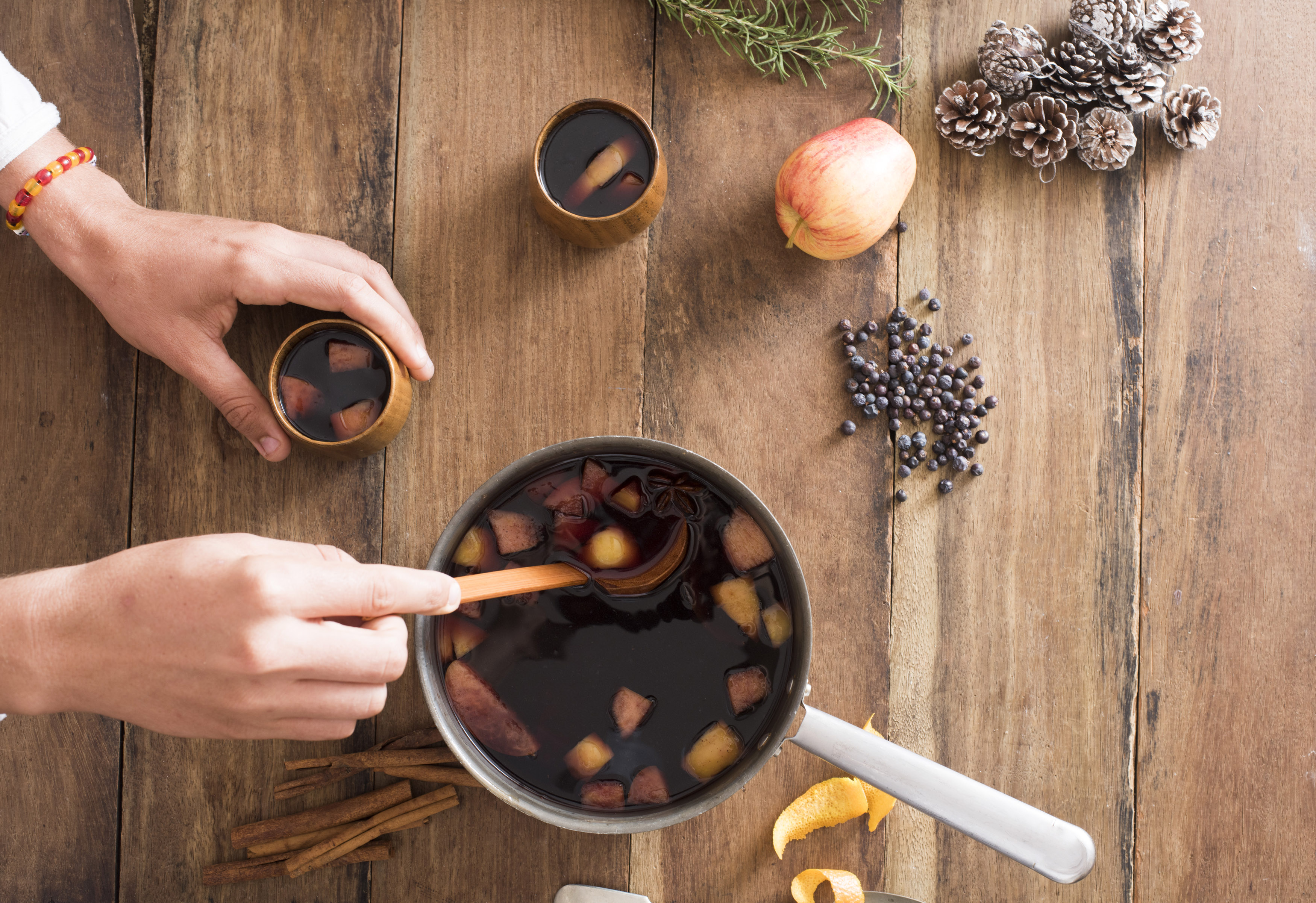 Person serving fresh hot mulled red wine with fruit and spices from a large pot into mugs using a ladle, overhead view with ingredients