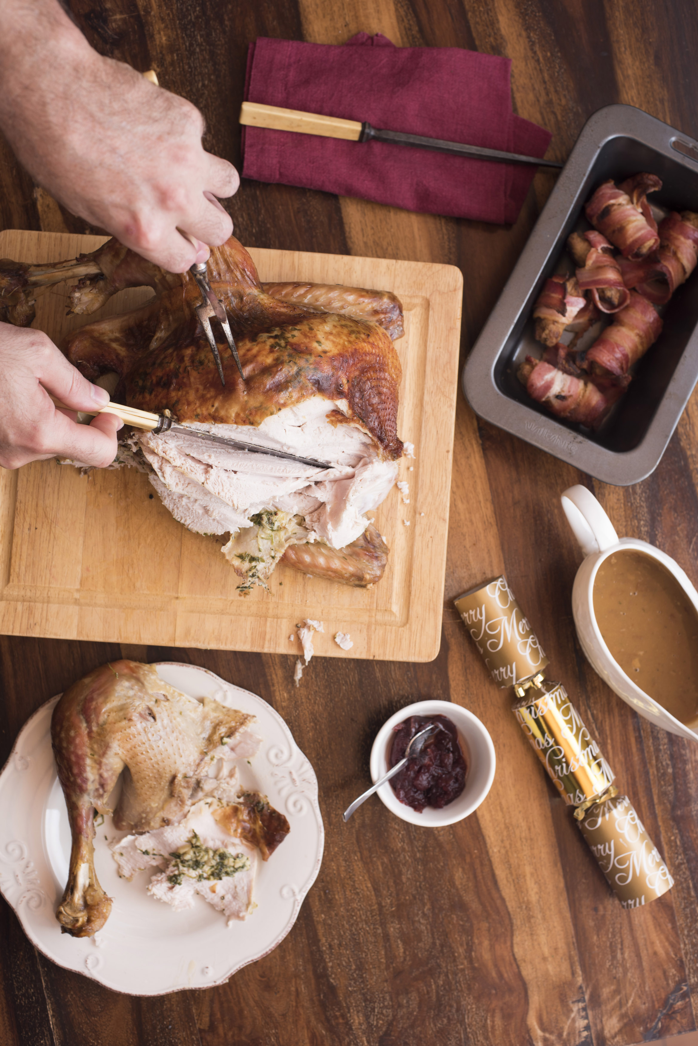 Man cutting thanksgiving turkey on wooden cutting board on a wooden table