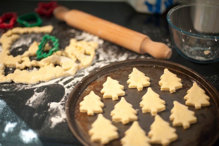 baking homemade christmas cookies with pastry cut out in the shape of traditional christmas trees arranged - Homemade Christmas Cookies