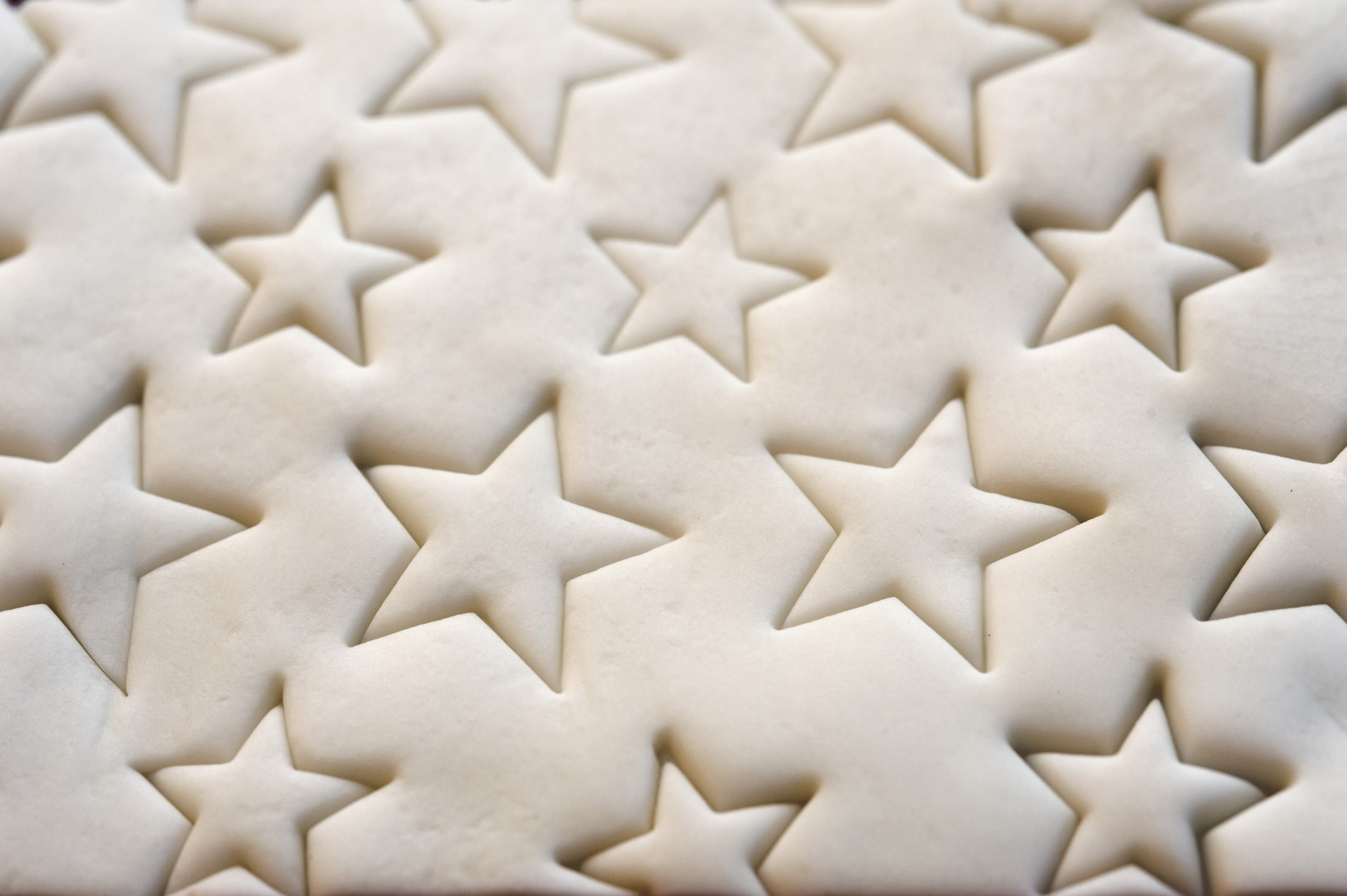 Decorative Christmas icing on top of a cake with a pattern or impressed stars, background close up view