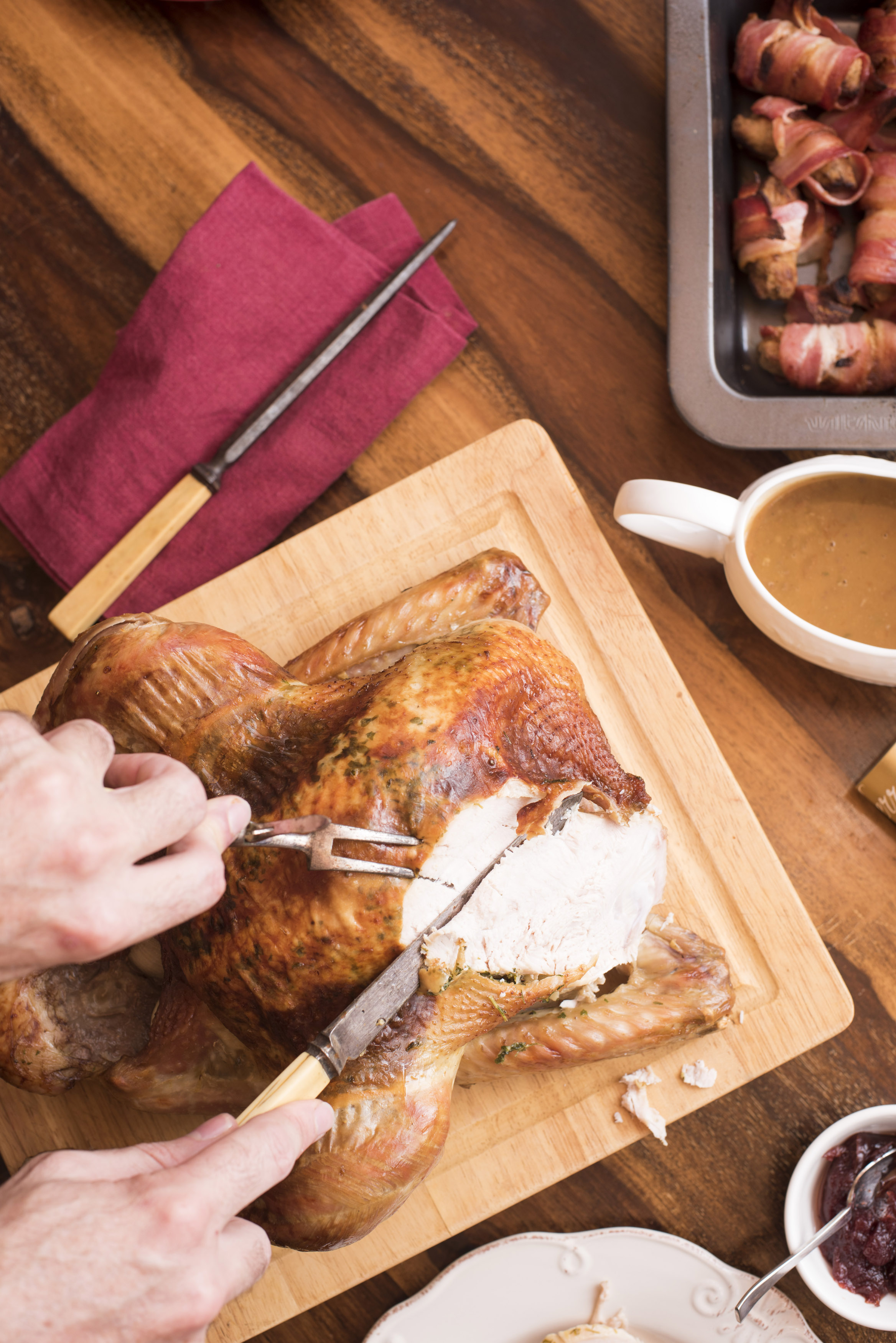 Man carving a Christmas roast turkey slicing the white meat of the breast at the table in a overhead view of his hands