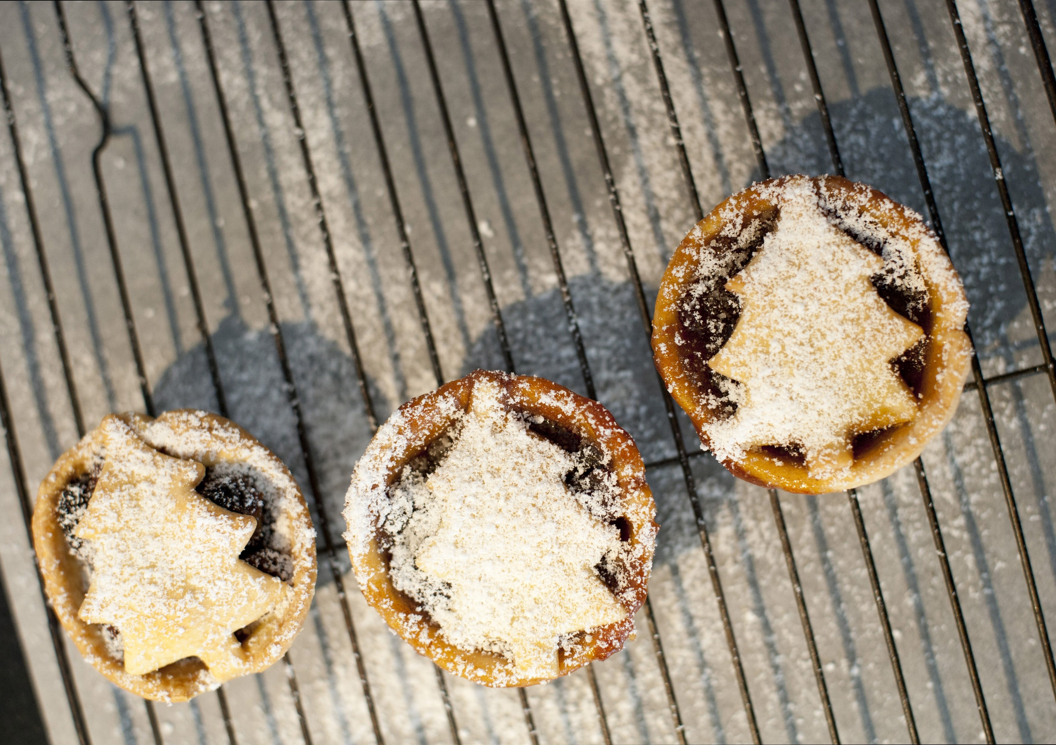 Overhead view of three freshly baked homemade delicious traditional Christmas mince pies decorated with Christmas tree pastry