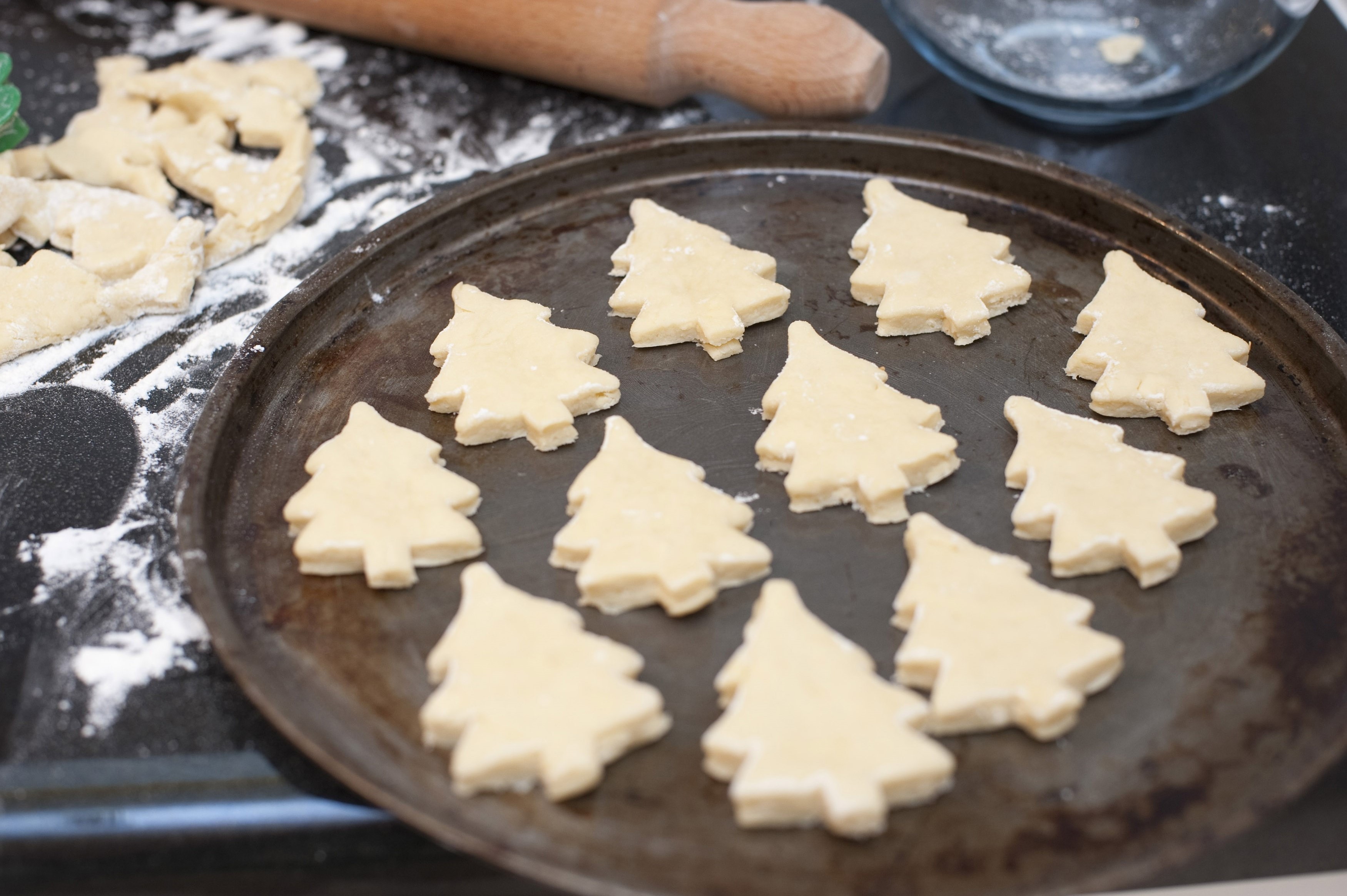Baking tray with Christmas cookies in the shape of Christmas trees ready for baking for traditional festive seasonal Xmas cuisine