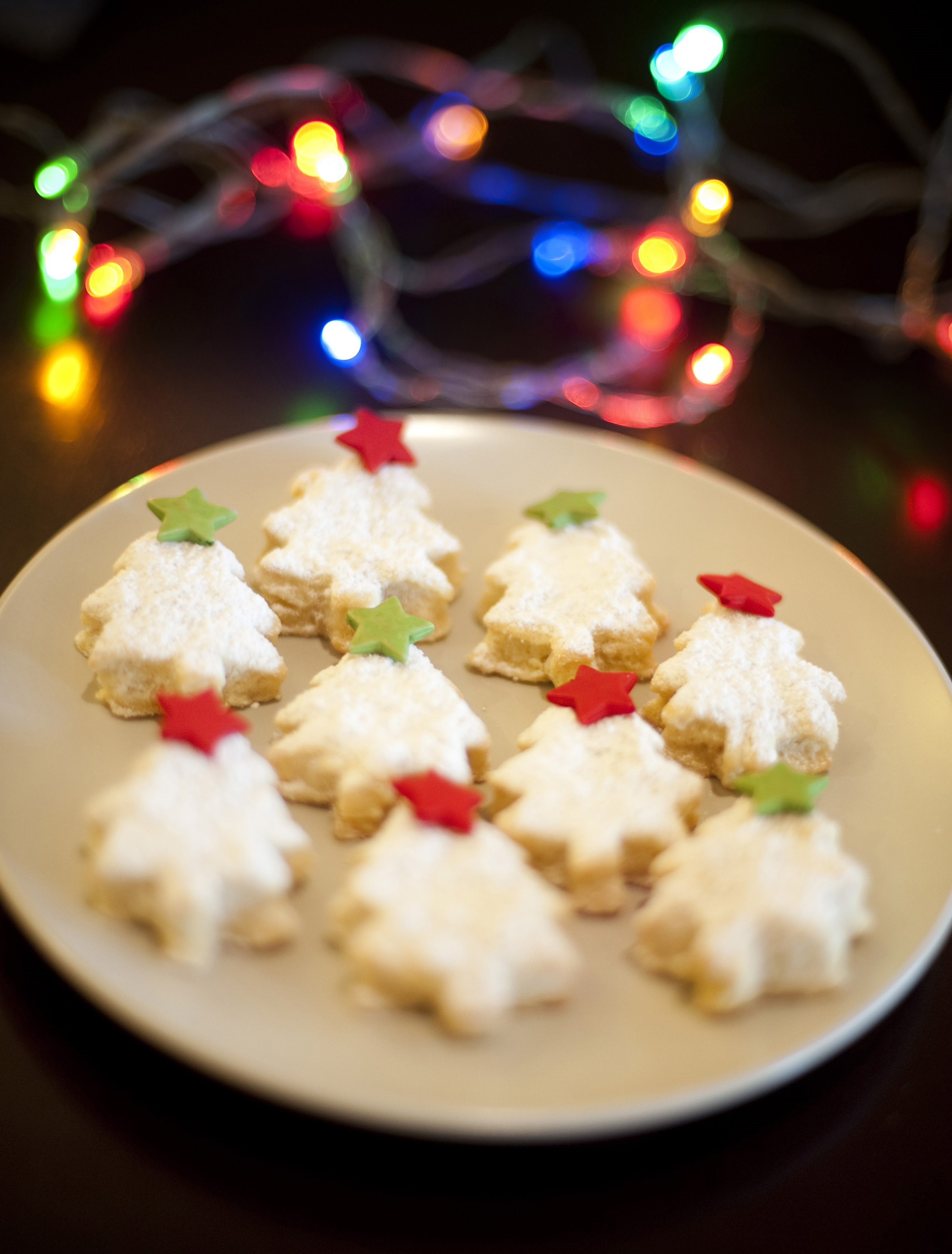 Festive Christmas cookies or biscuits n the shape of traditional Christmas trees decorated with little red and green stars with colourful party lights in the background