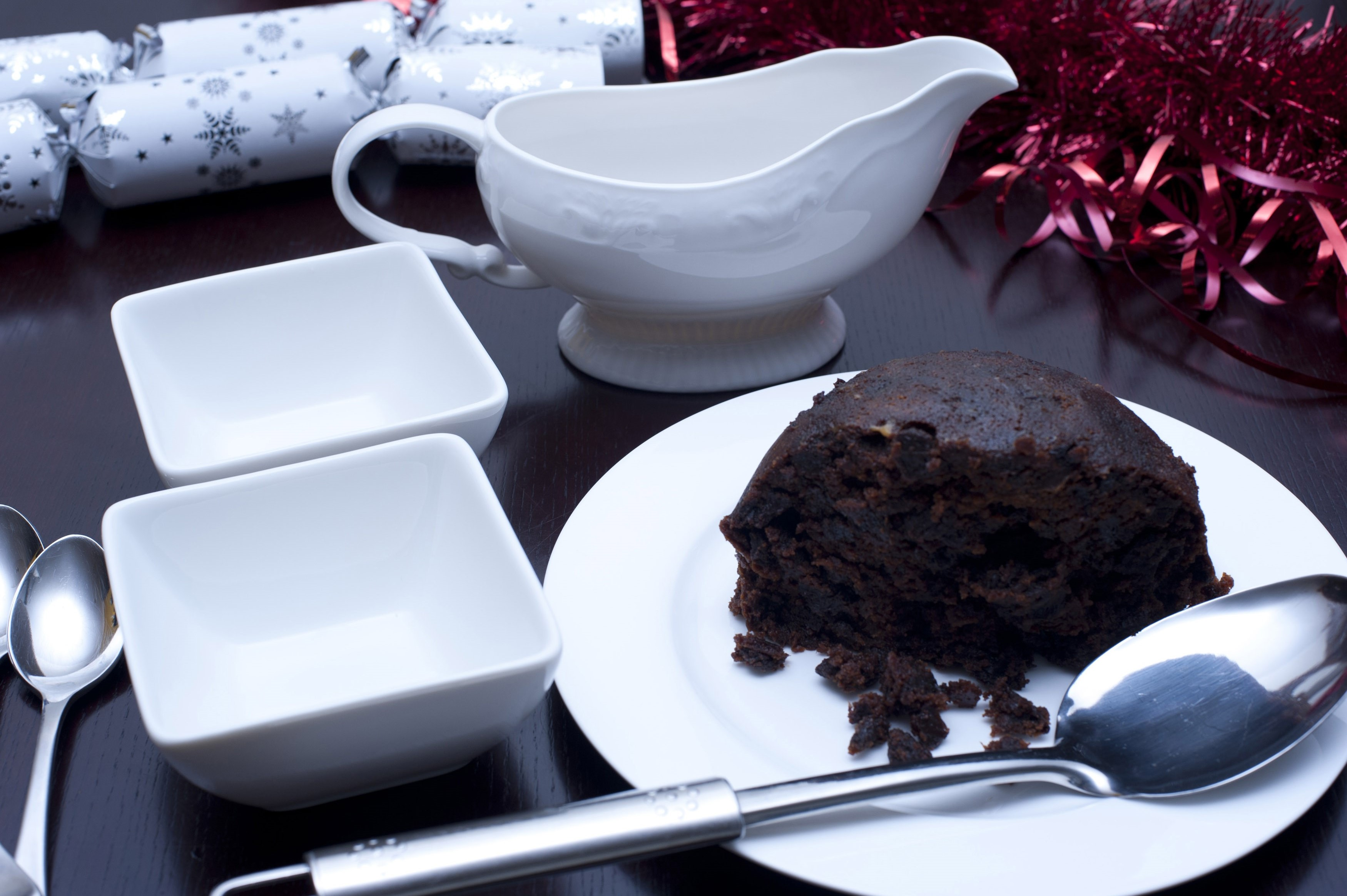 Rich fruity boiled Christmas pudding half eaten on a plate with two dishes for serving dessert for a festive seasonal meal