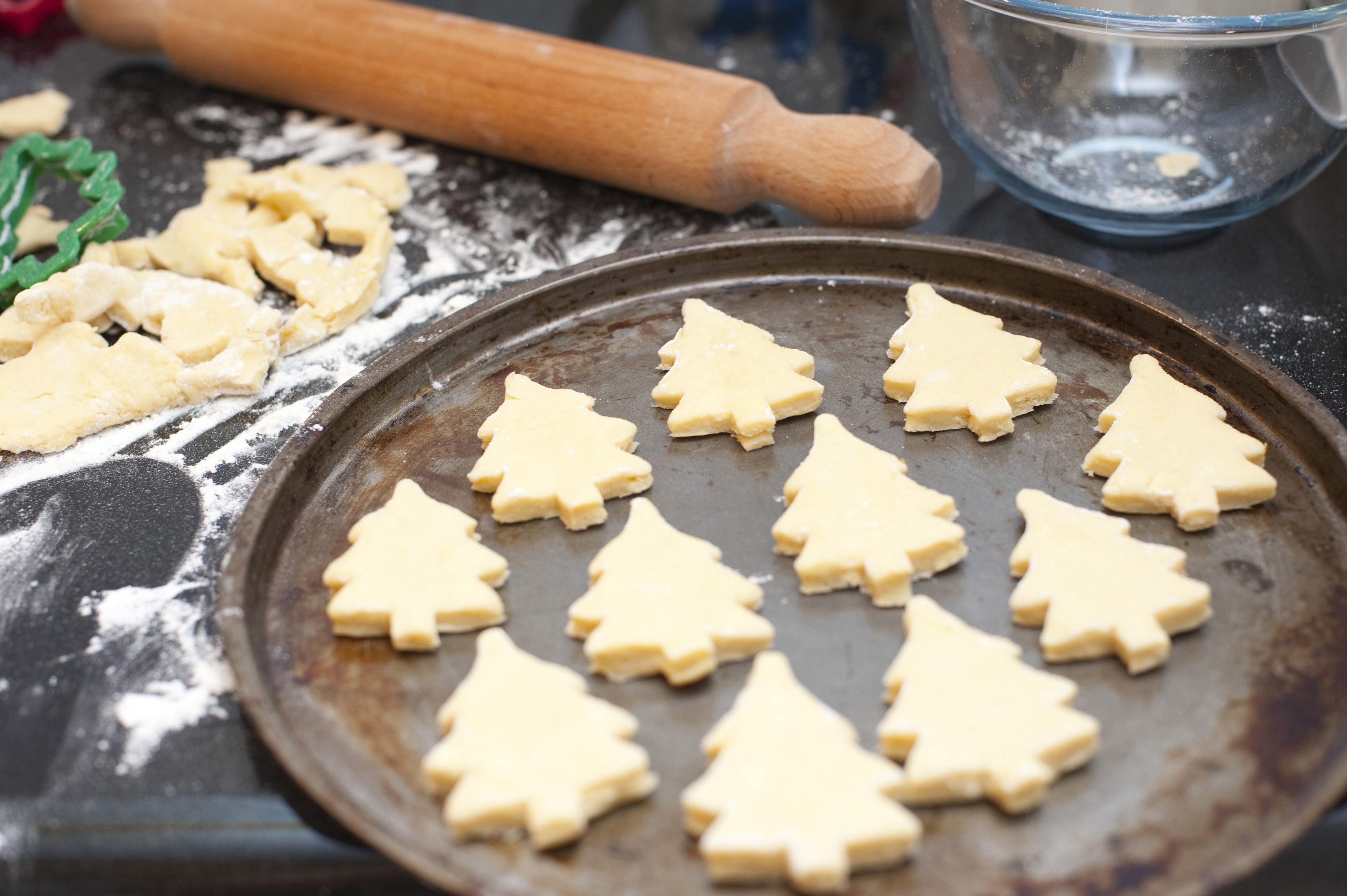 Freshly baked Christmas tree biscuits in golden pastry arranged on the baking tray having just been removed from the oven during preparation of the recipe