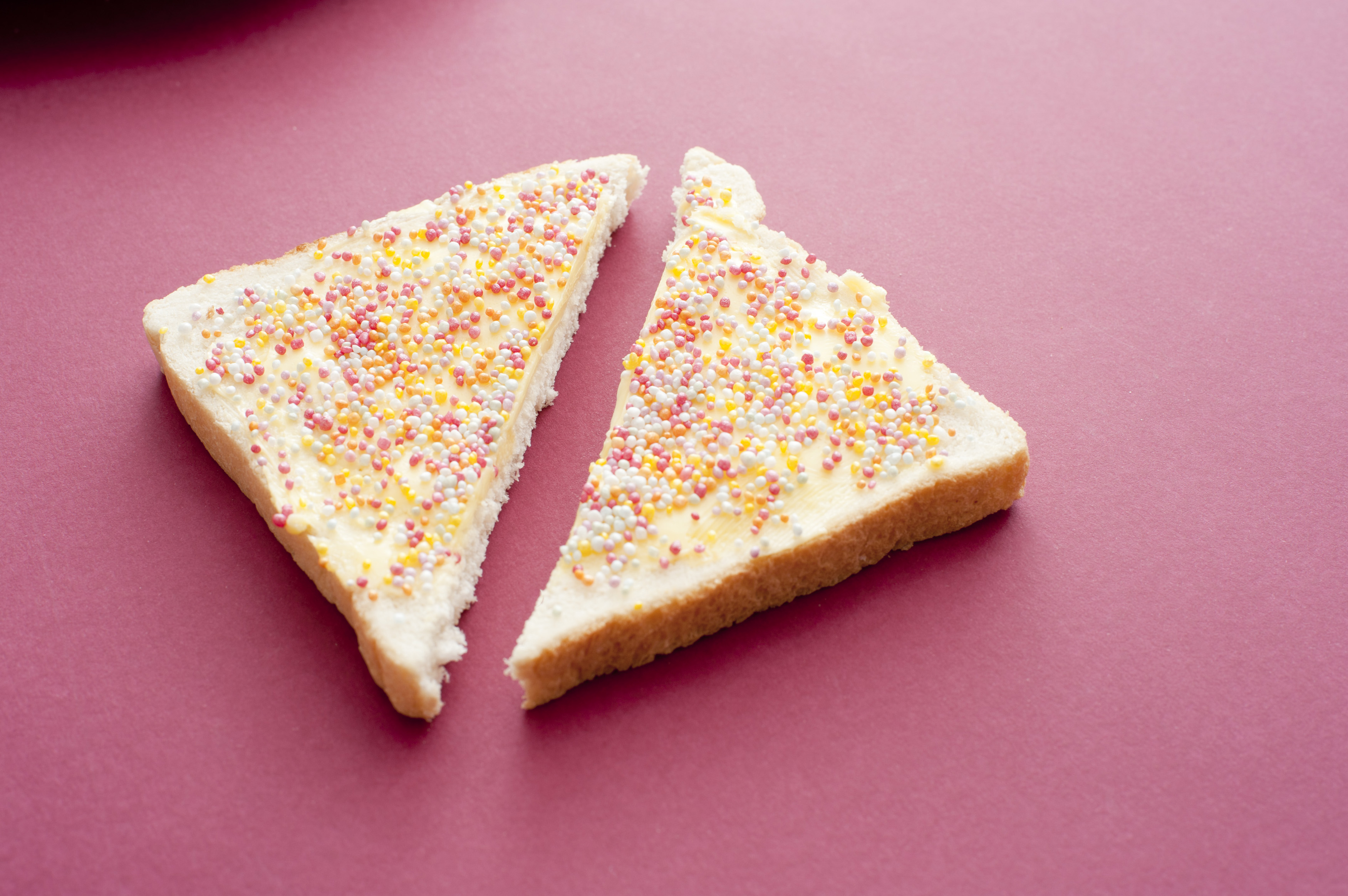 Slice of Australian fairy bread with colorful sprinkles, sugar candy pearls or hundreds and thousands spread over the surface on a red back ground with copy space