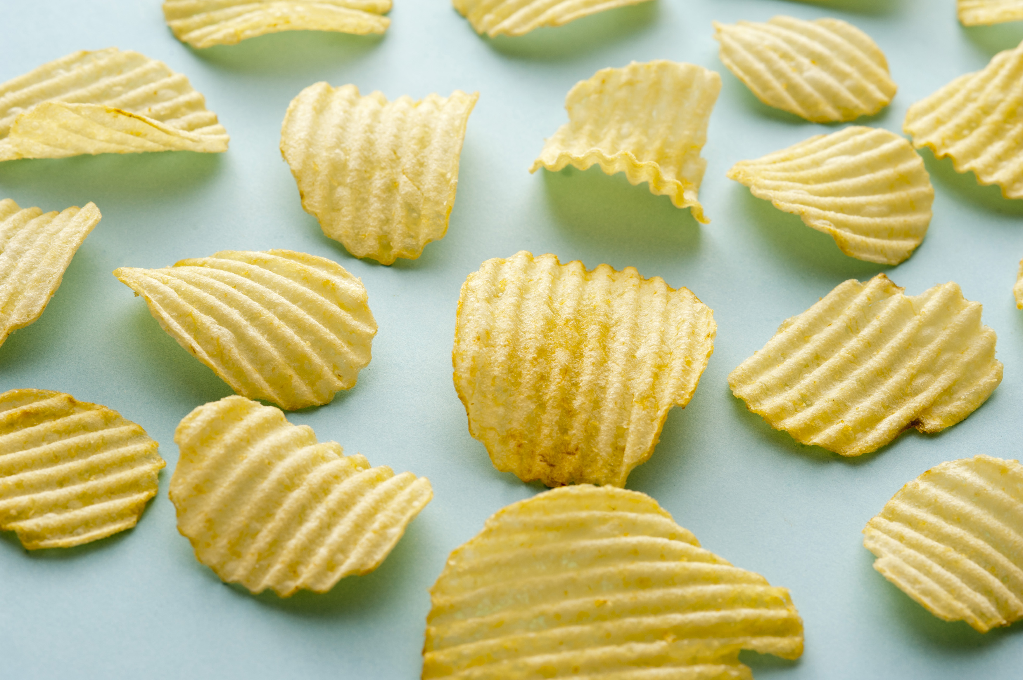 Scattered arrangement of crinkle cut potato crisps or chips on a green background viewed at an oblique high angle