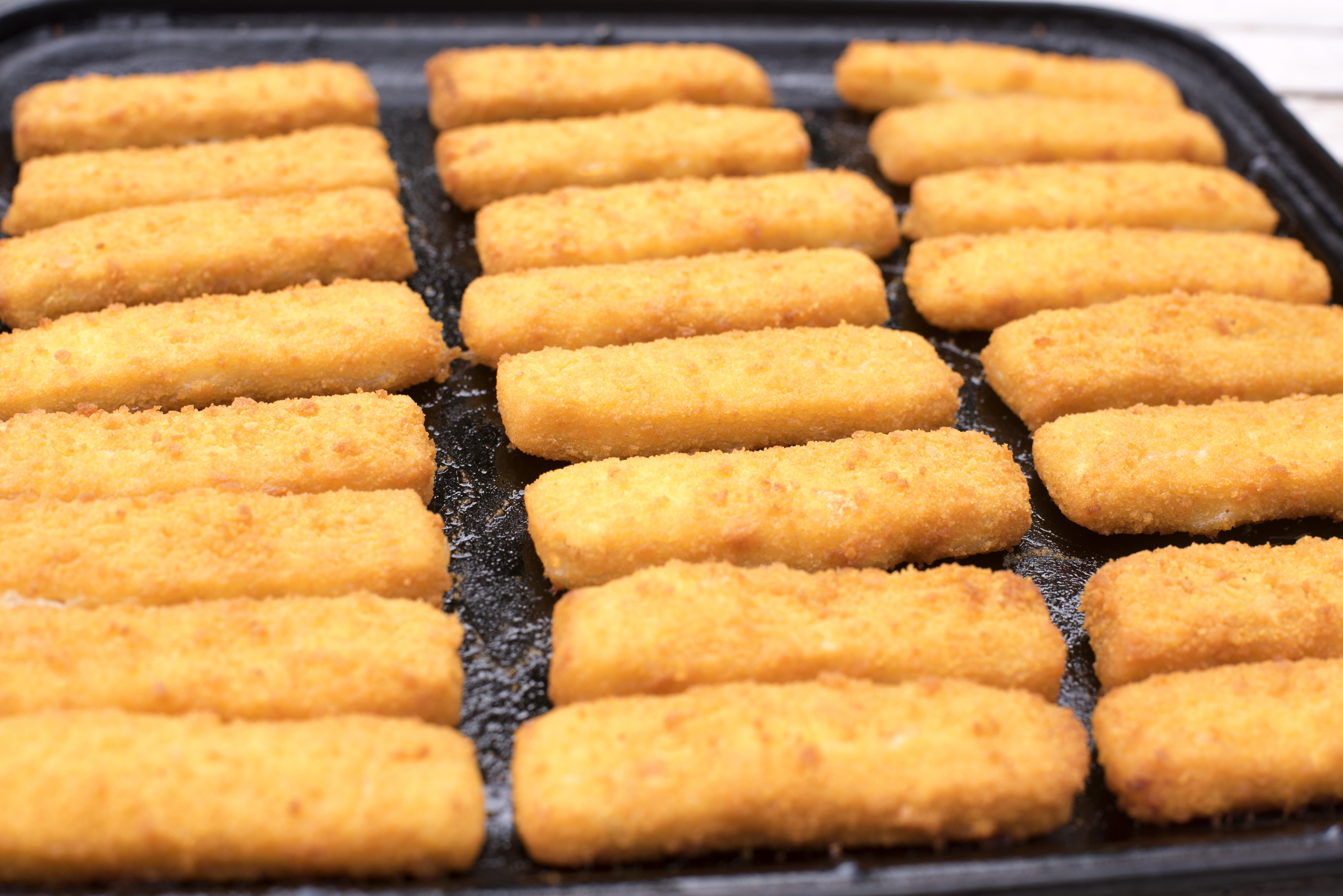 Full frame close up on freshly baked fish finger snacks on black oven tray for concept about breaded comfort food