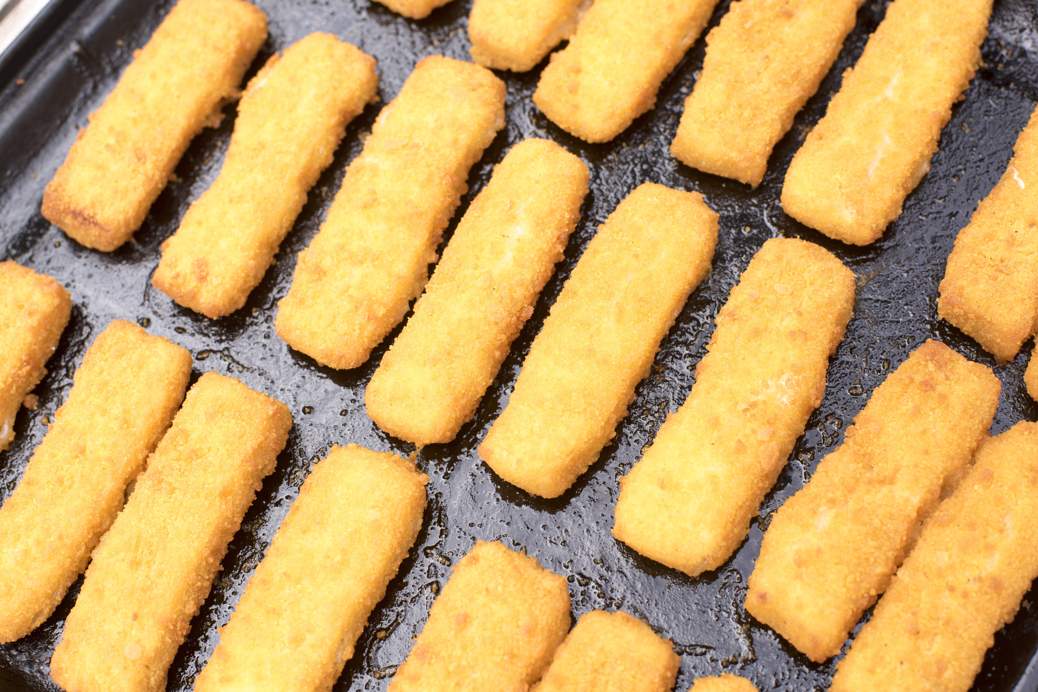 Crumbed fish fingers laid out neatly on a baking tray for coking in a close up high angle view