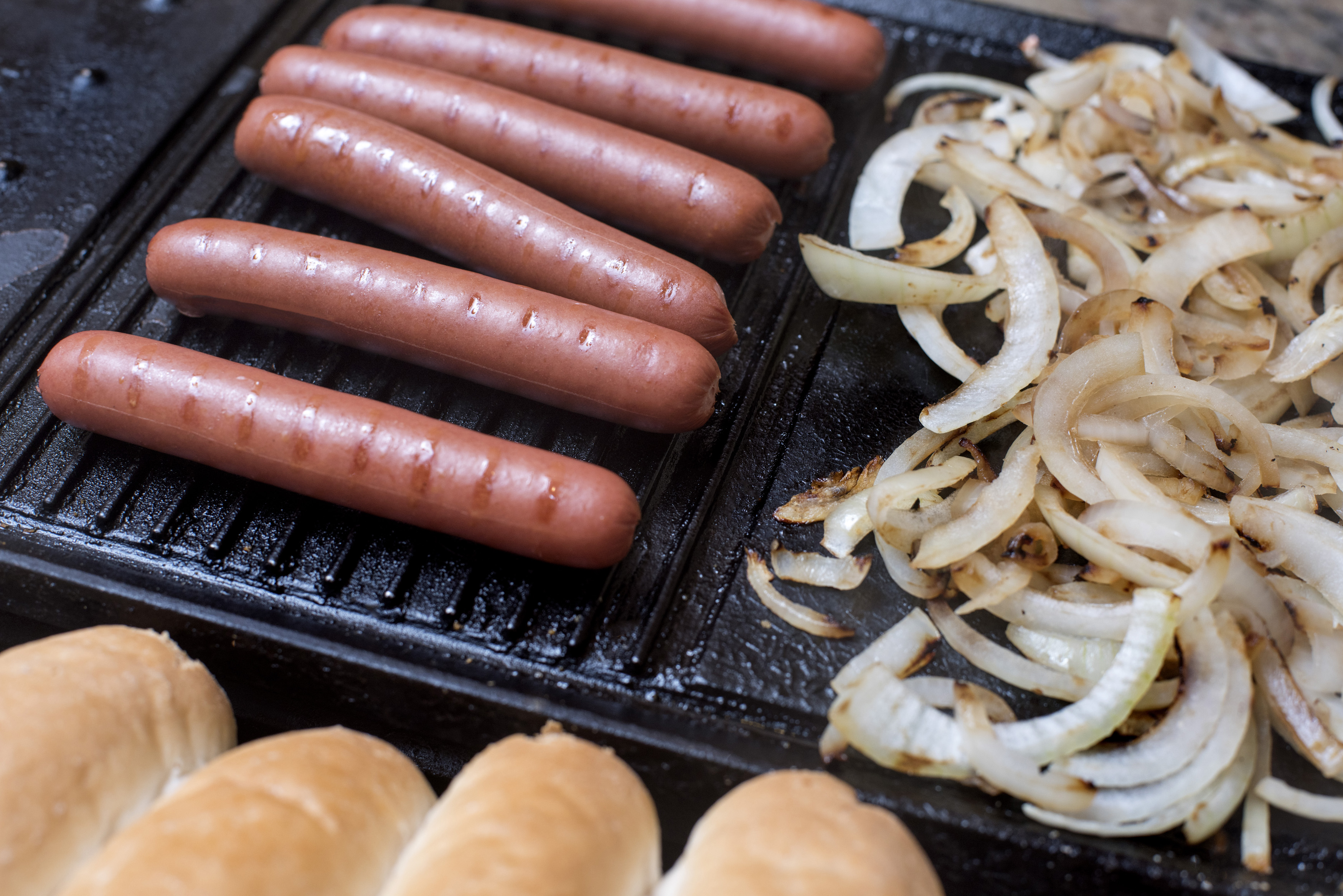 Preparing a tasty hot dog on a grill with smoked Wiener sausages, diced onions and fresh white bread rolls