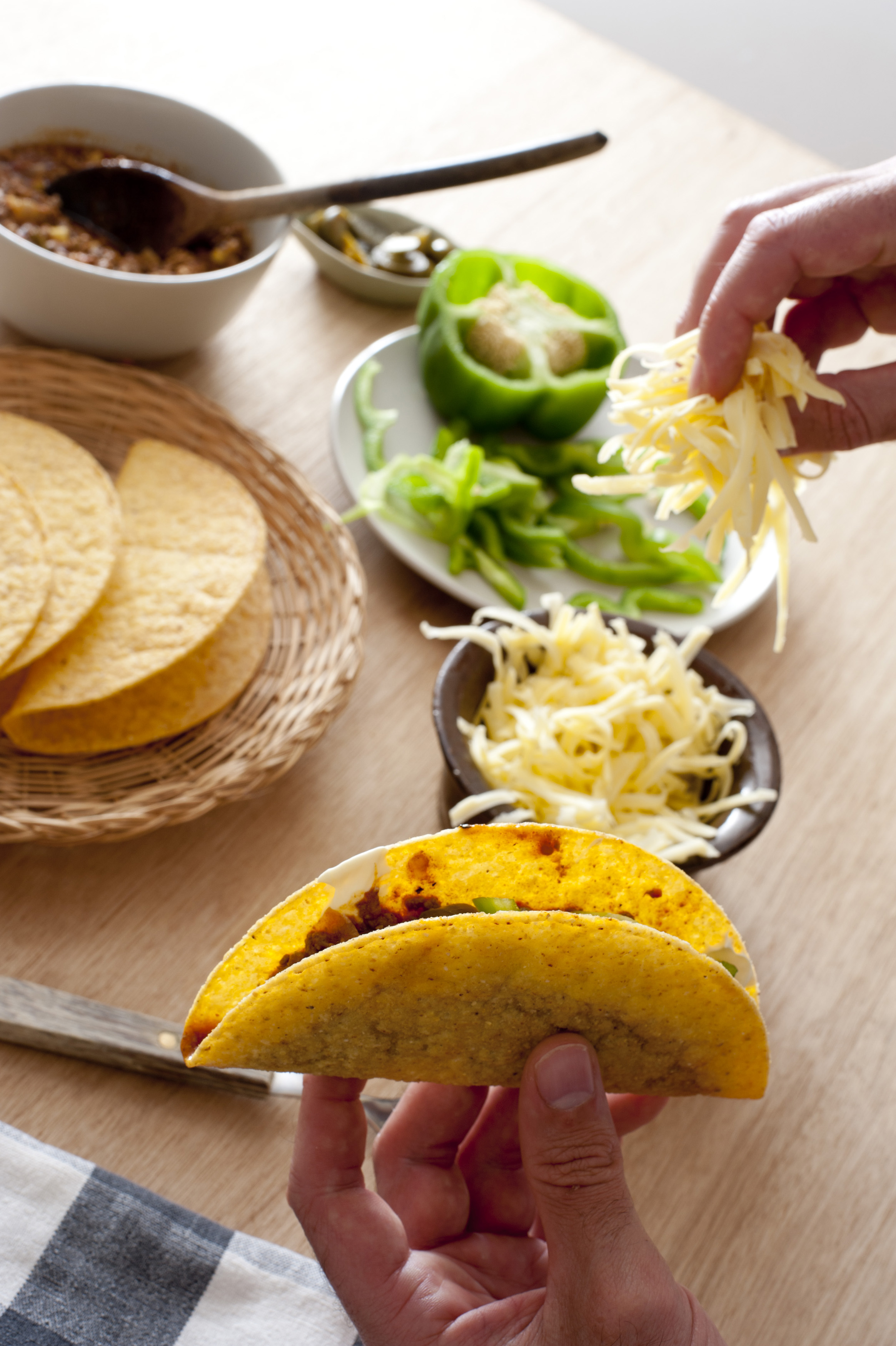 Man preparing corn tortillas adding grated cheese, fresh green bell pepper and minced savory beef