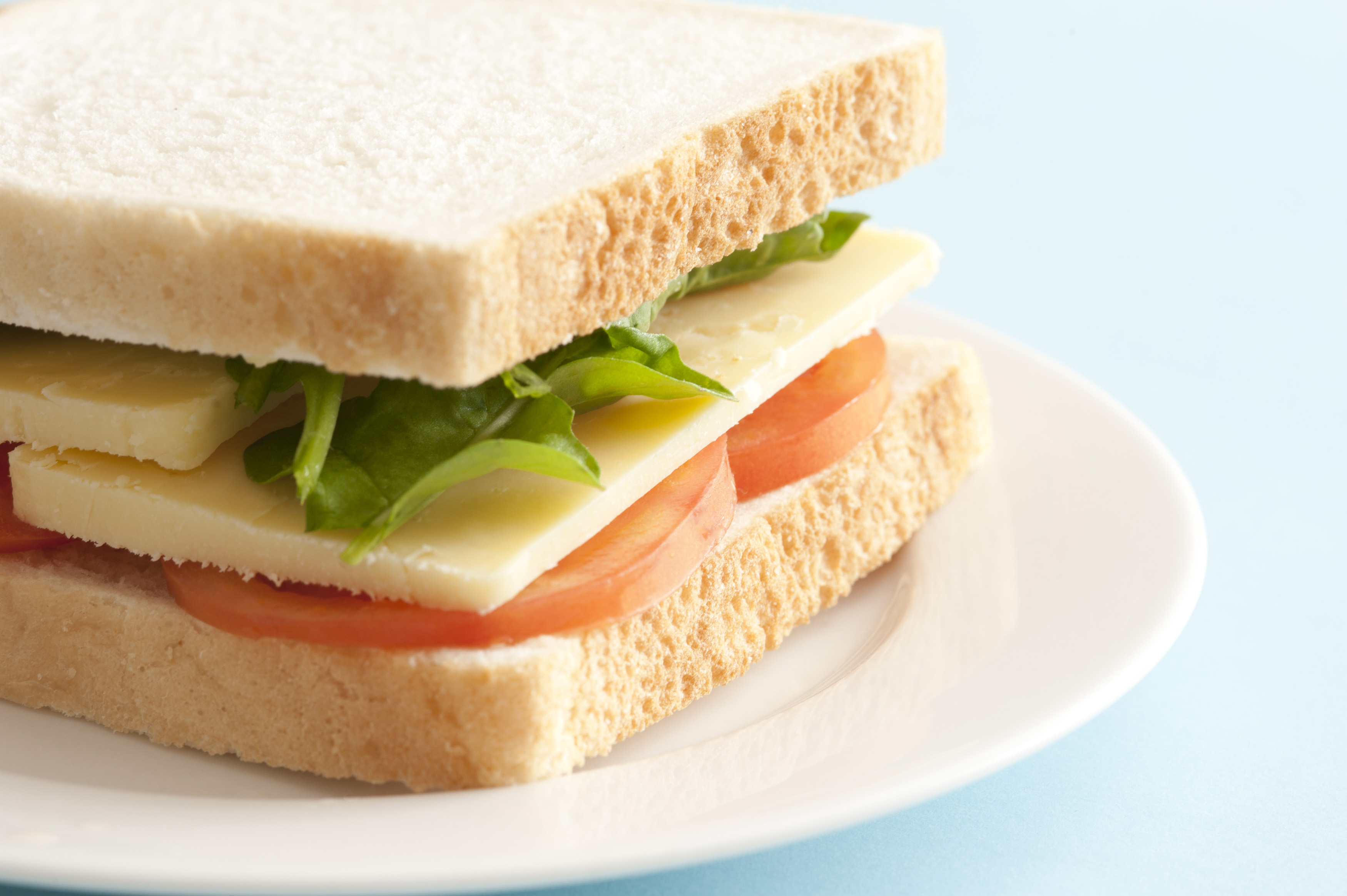 Close up on side of sandwich with thick slices of yellow cheese, green lettuce leaves and round tomato slices on plate over blue