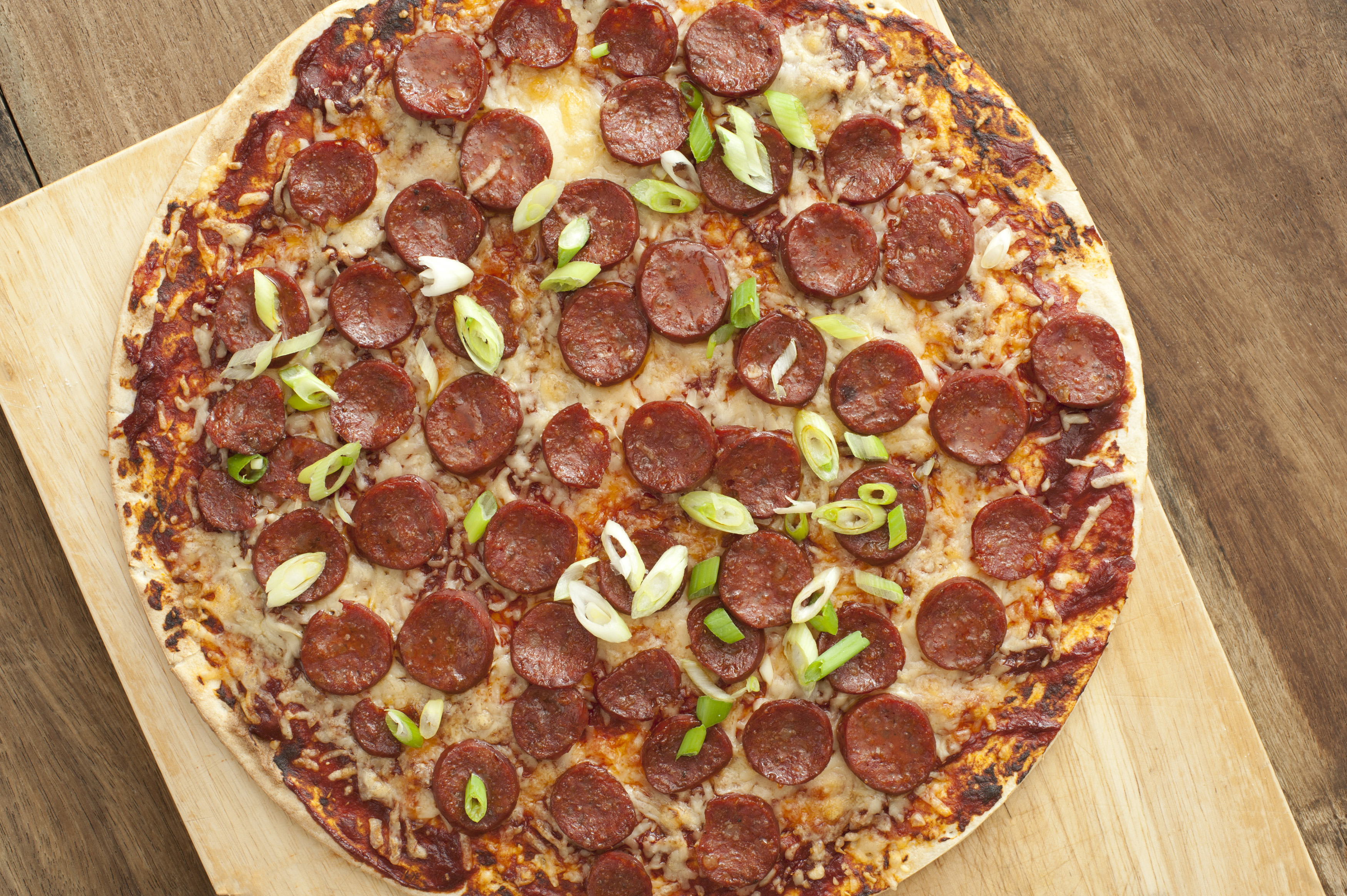 Whole pepperoni or salami pizza with mozzarella cheese and shallots on a crispy thin crust viewed from above on a wooden cutting board
