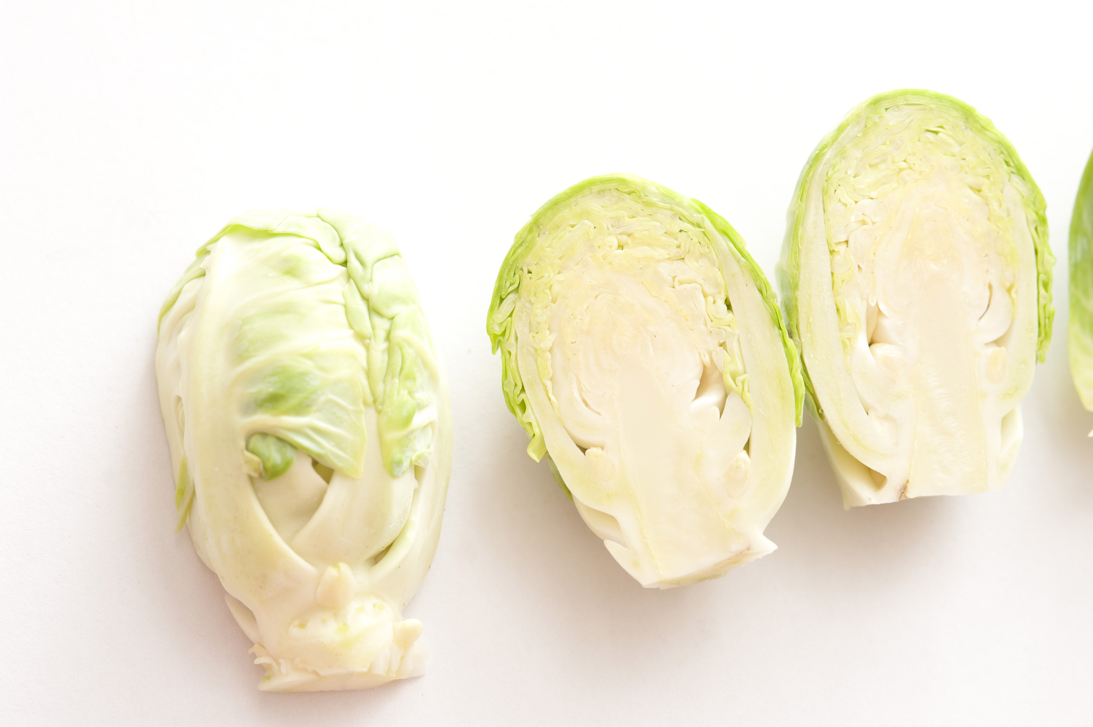 A close up of halved brussel sprouts on a white background.