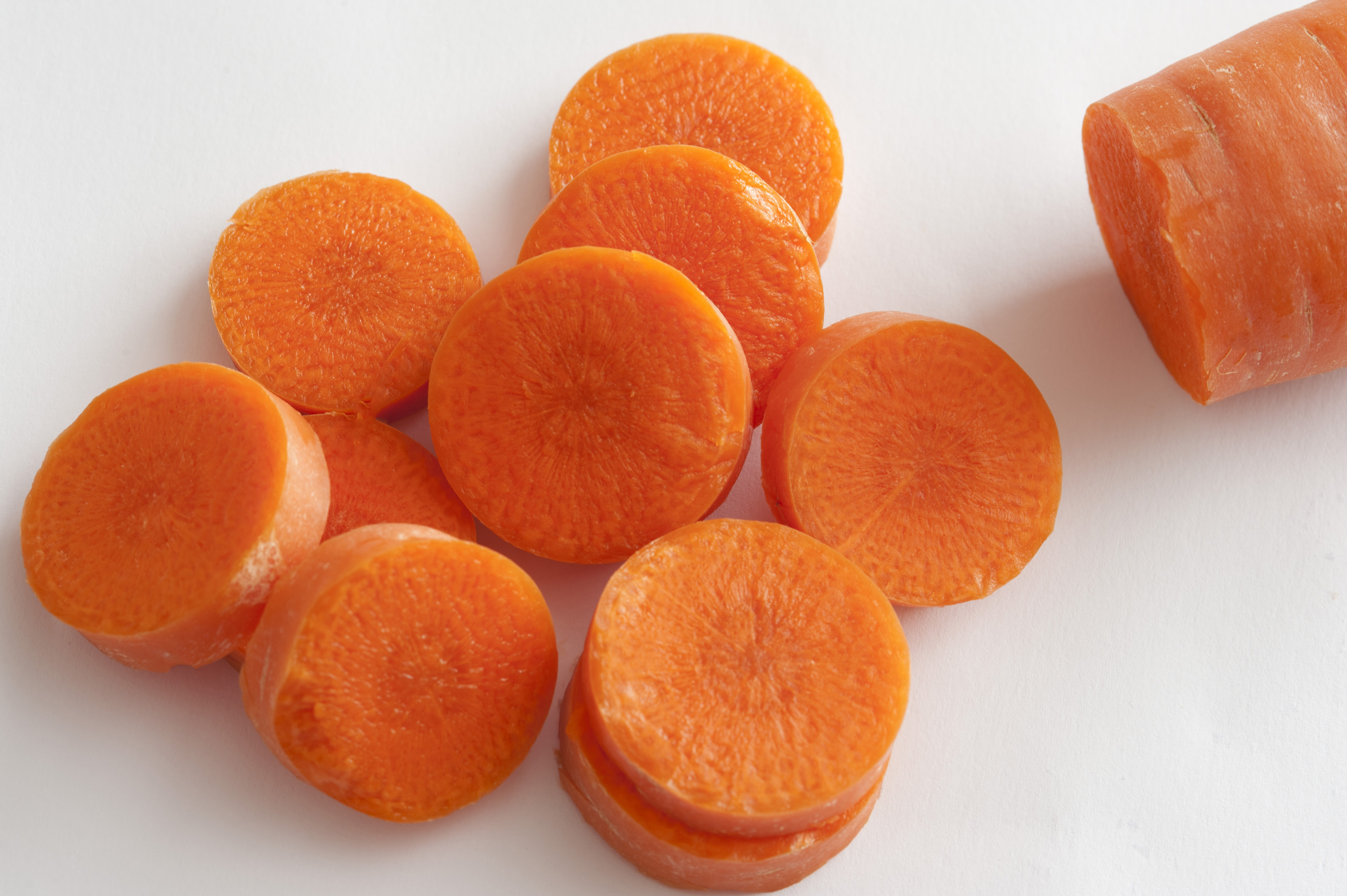 Heap of sliced fresh raw carrot with the tip of the remainder visible alongside ready for use in a salad or cooking, over white