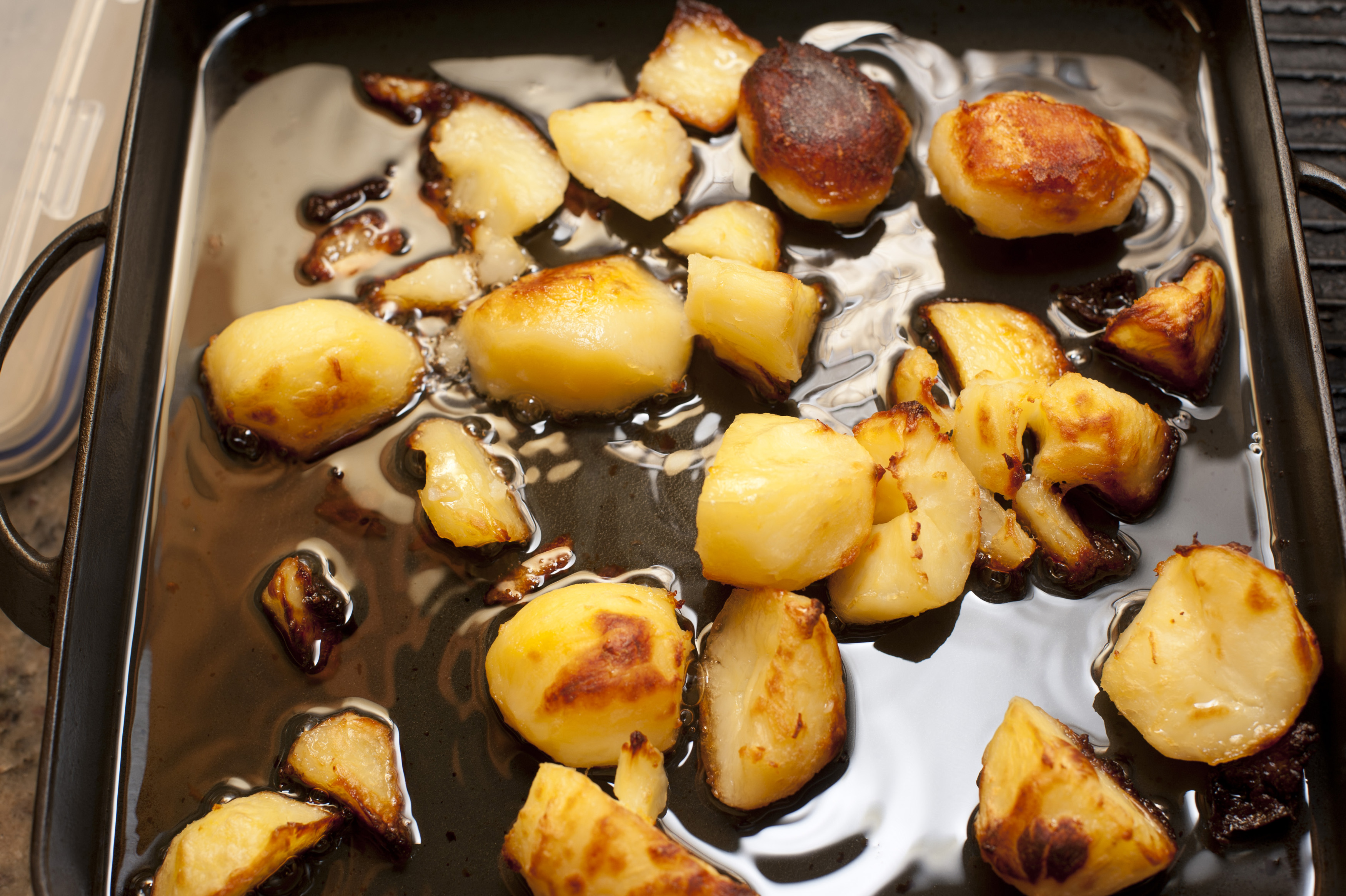 Crispy golden roast potatoes in an oily grill pan waiting to be served for dinner, close up high angle view