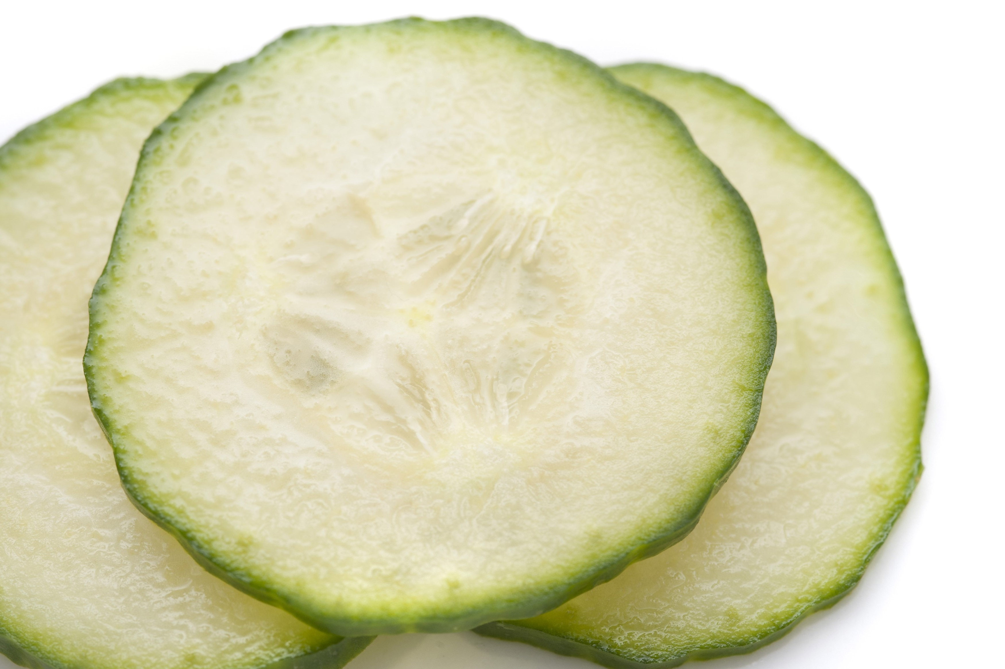 Close up of thinly sliced cucumber showing pip, pulpy flesh and rind detail for use as a salad ingredient