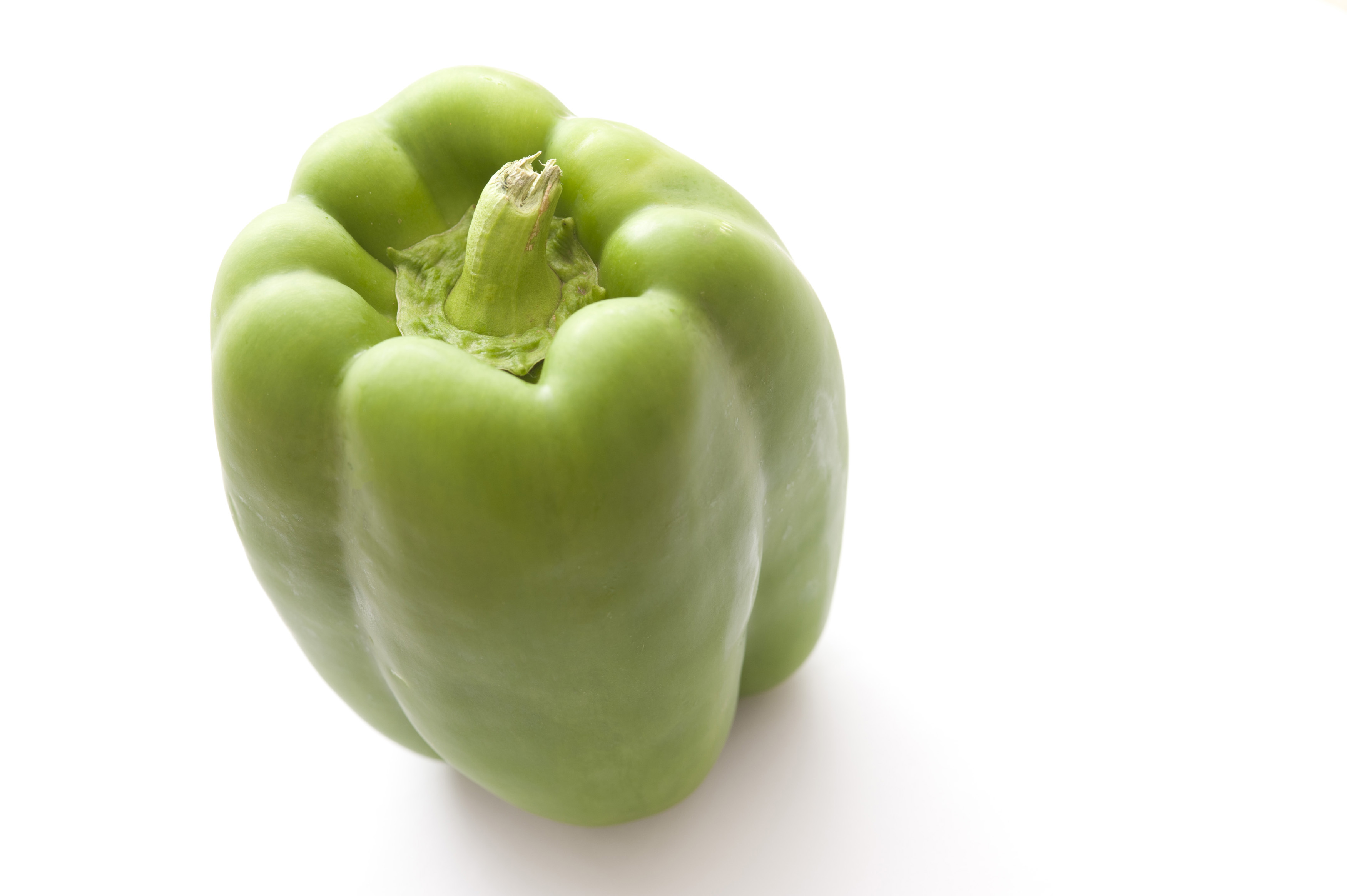 Fresh whole raw green bell pepper, sweet pepper or capsicum on a white background with copyspace, high angle view