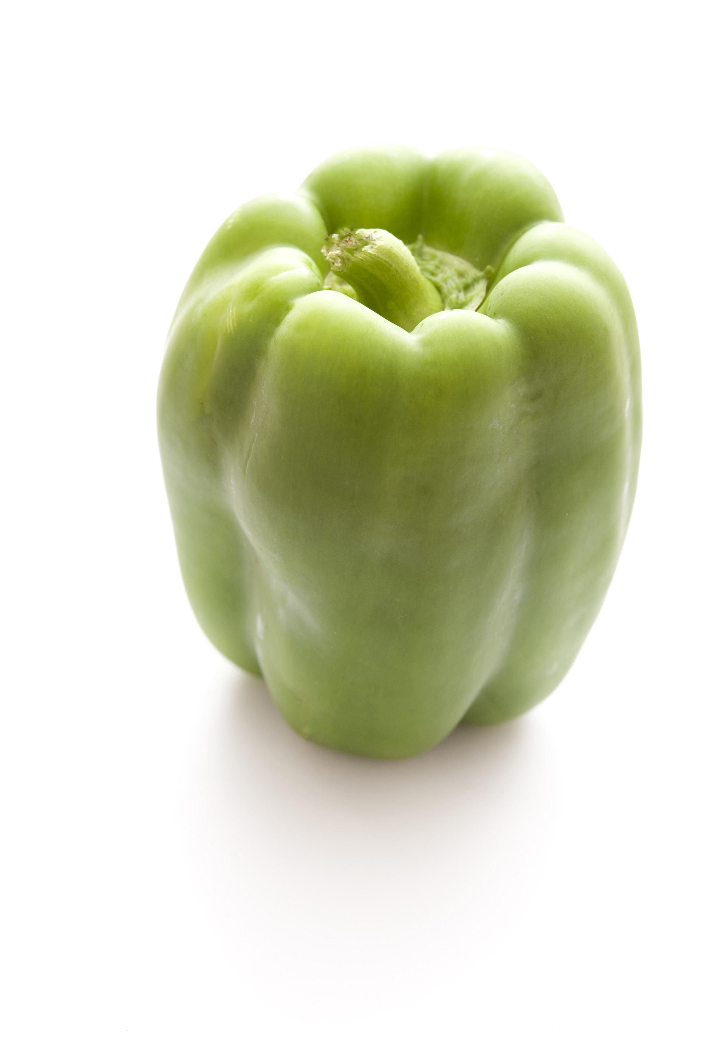 Fresh whole green sweet pepper, capsicum or bell pepper used in salads, as a cooking ingredient and in vegetarian cuisine, over white with copyspace