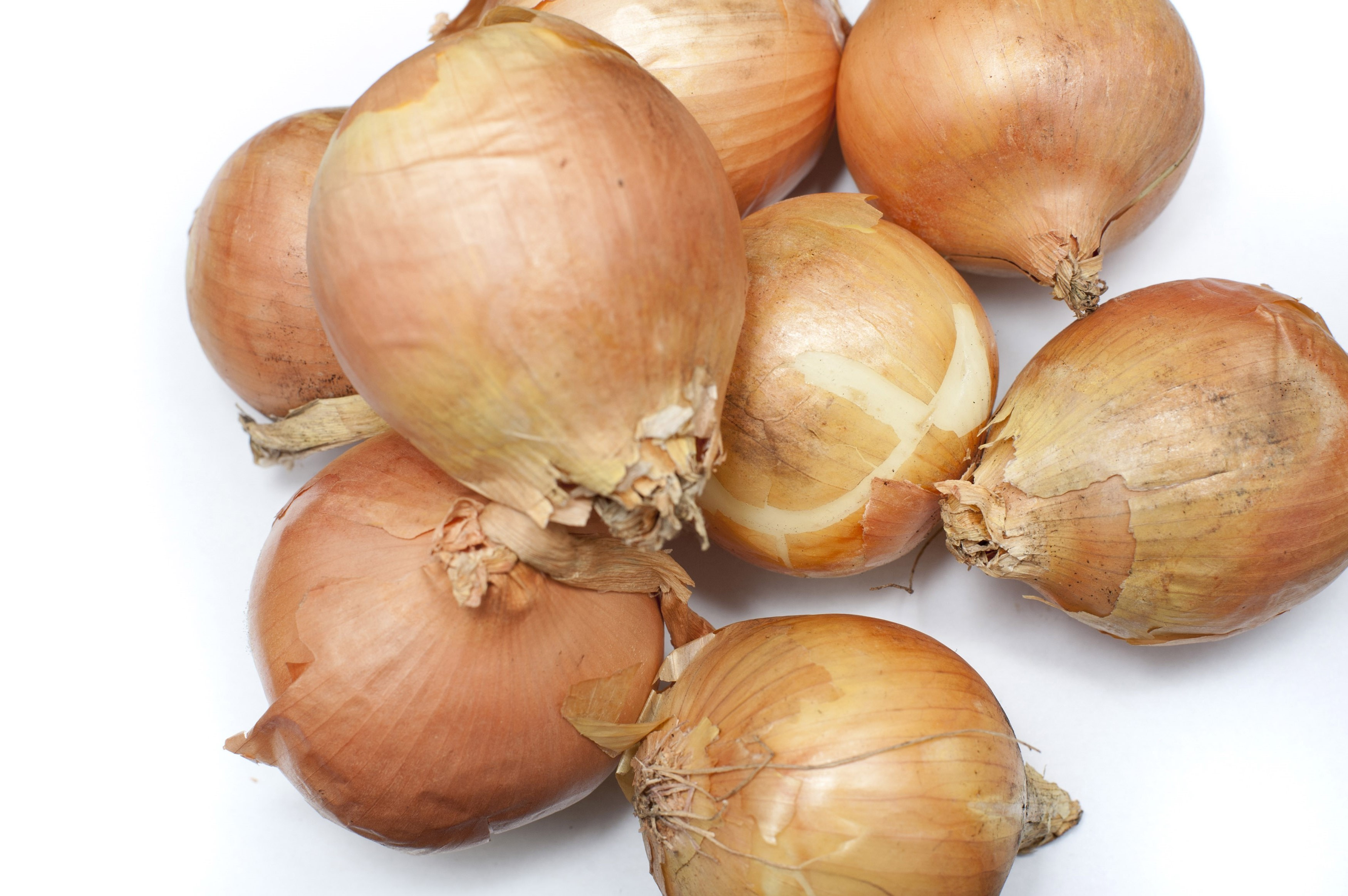 Pile of fresh whole raw brown onions, a pungent aromatic vegetable used in cooking as a flavouring