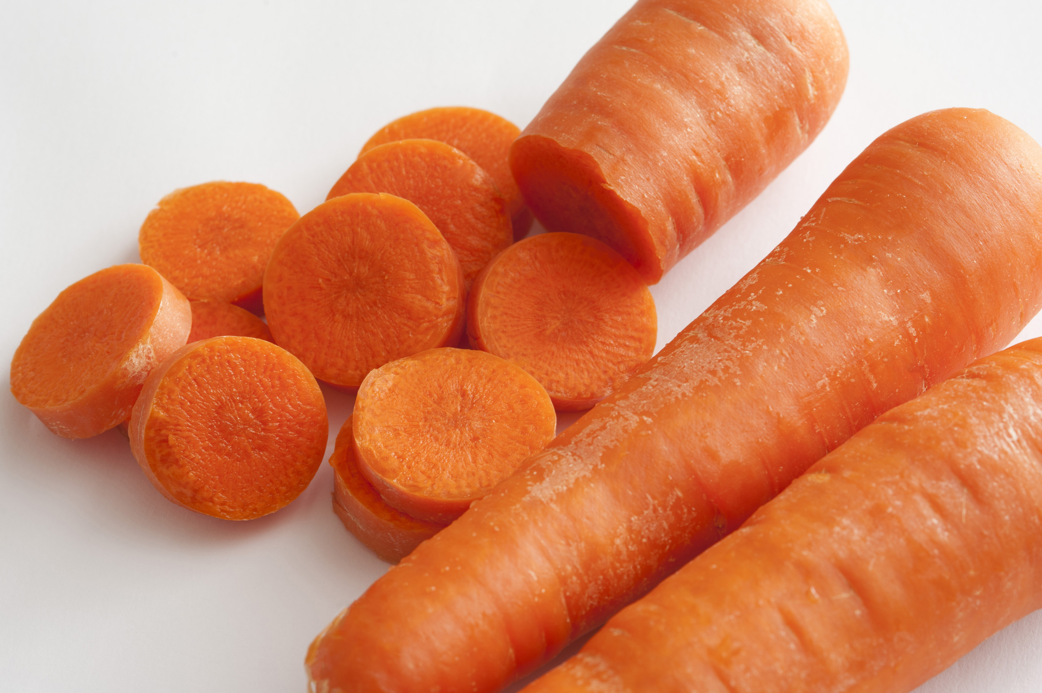 Close-up of pile of carrots on white background.