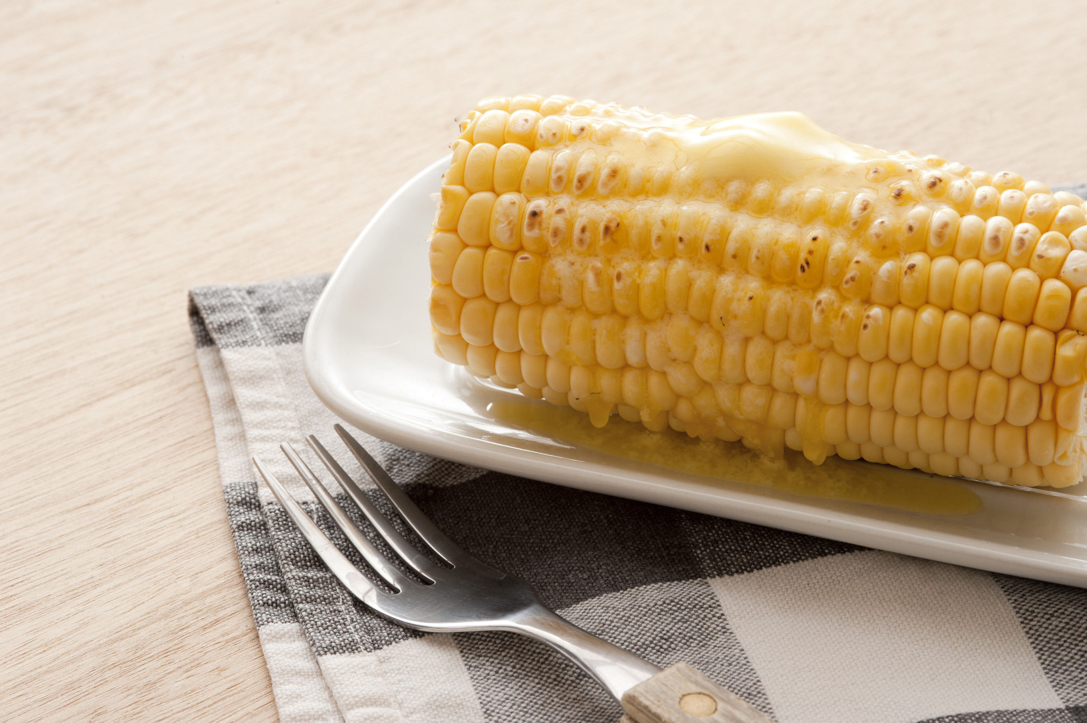 Cooked sweet corn on the cob topped with a dab of butter for a delicious snack or lunch, close up side view on a plate