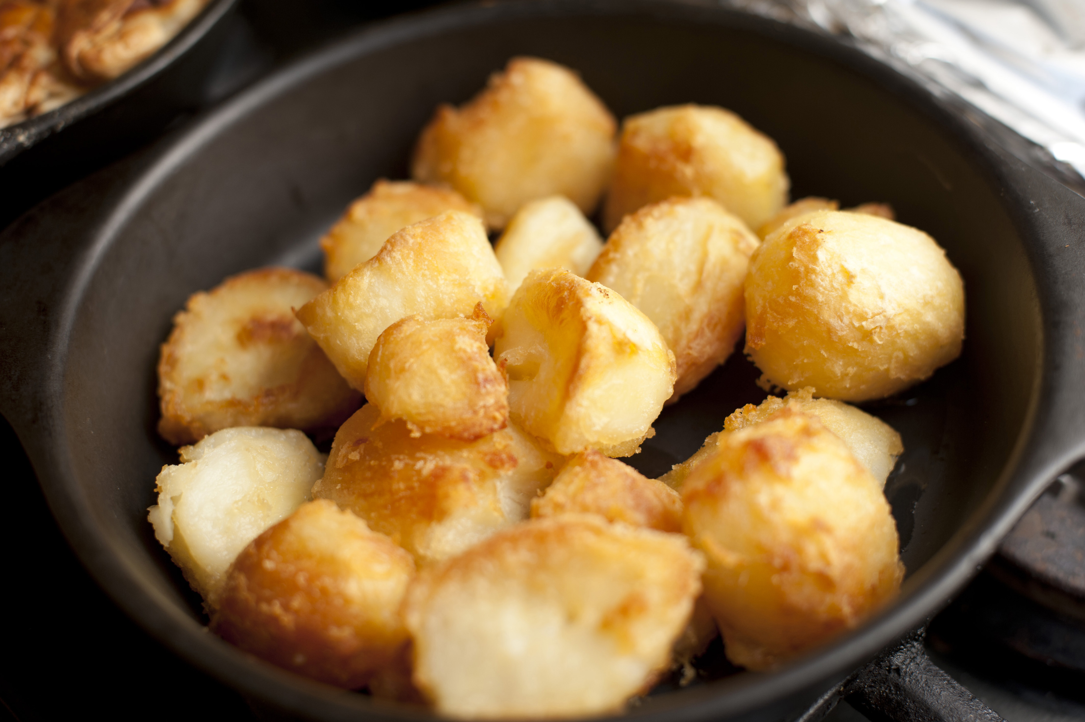 Close-up of delicious golden roast potatoes on in a skillet