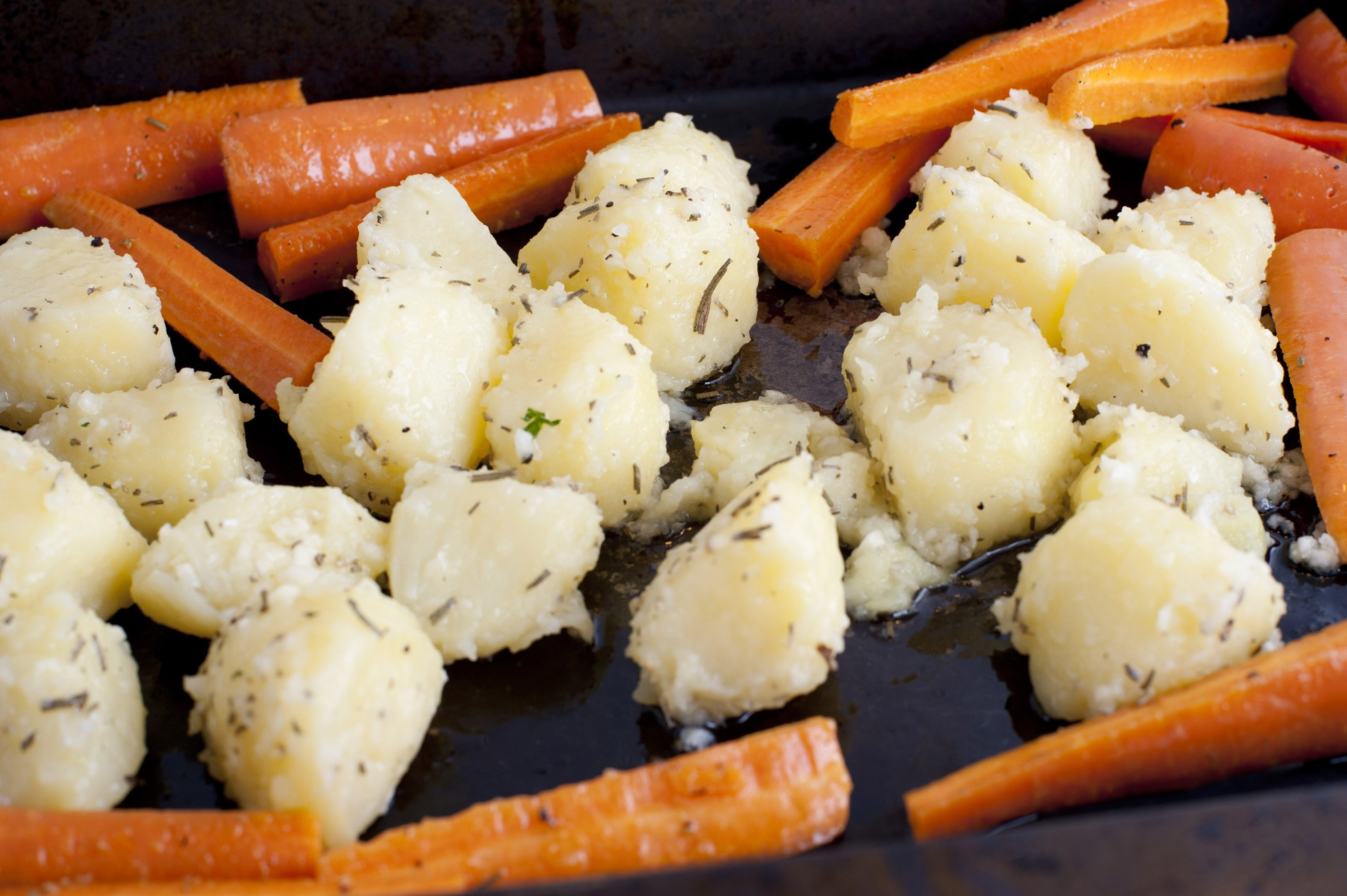 Vegetables being prepared for oven roasting with peeled diced parboiled potatoes and fresh carrots laid out on a roasting pan