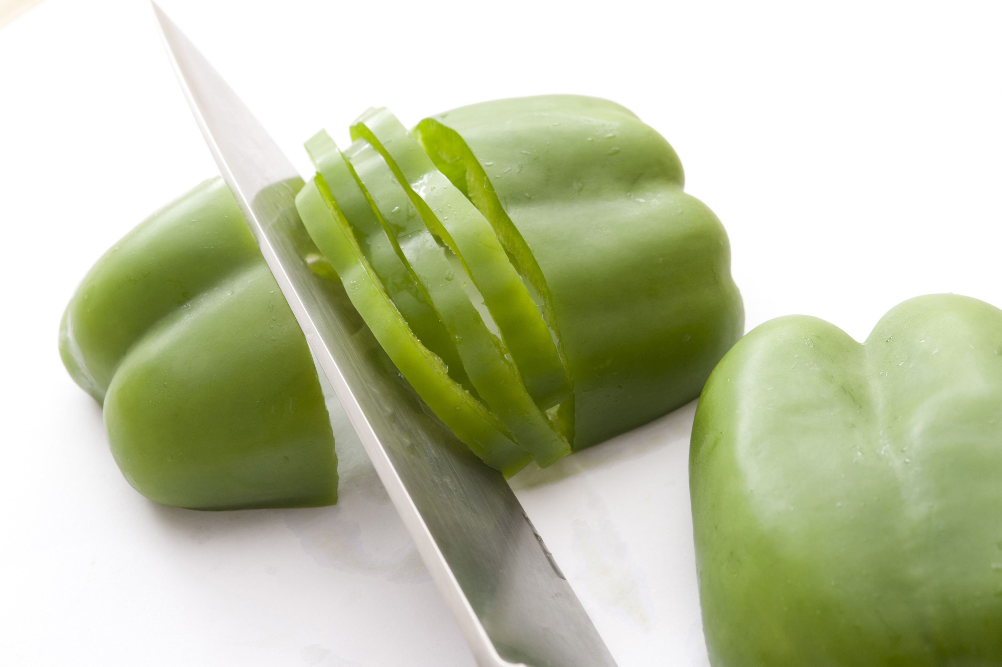 Cut green pepper with knife on white background