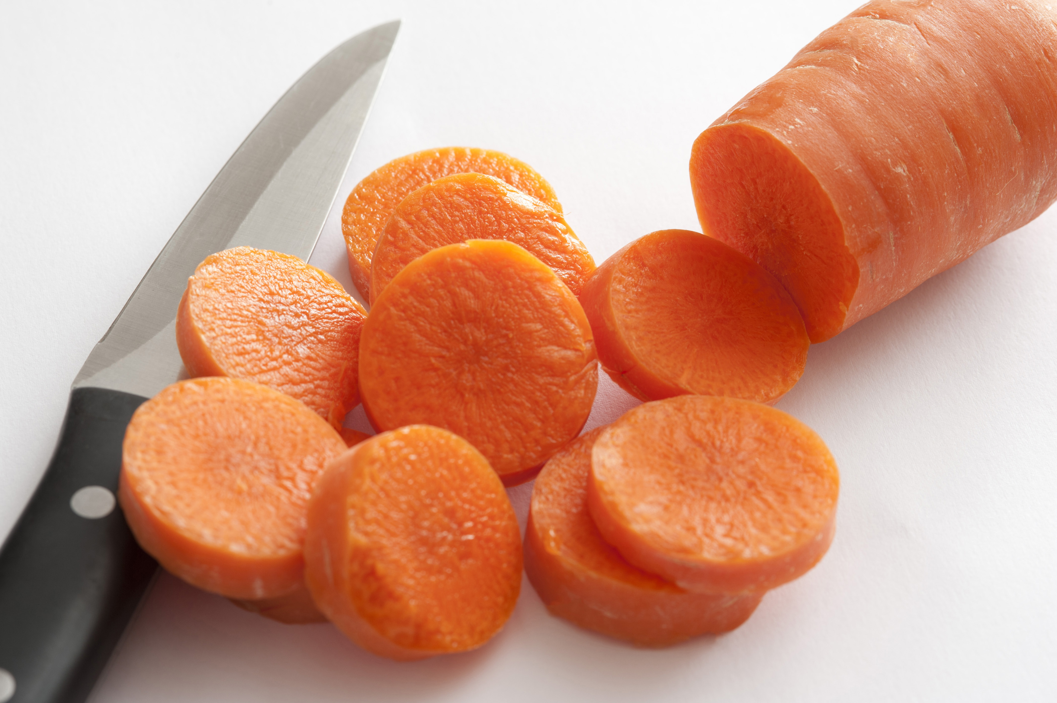 Close-up of cut carrot and knife on white background