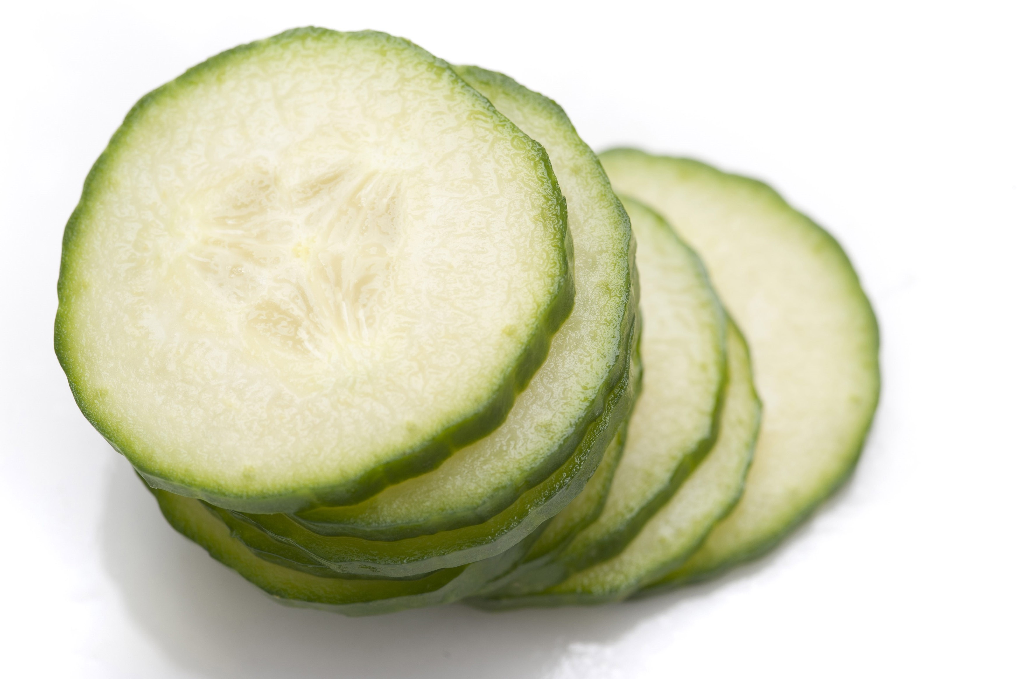 Stack of thin cucumber slices with focus to the top slice showing texture detail of the succulent flesh and pips