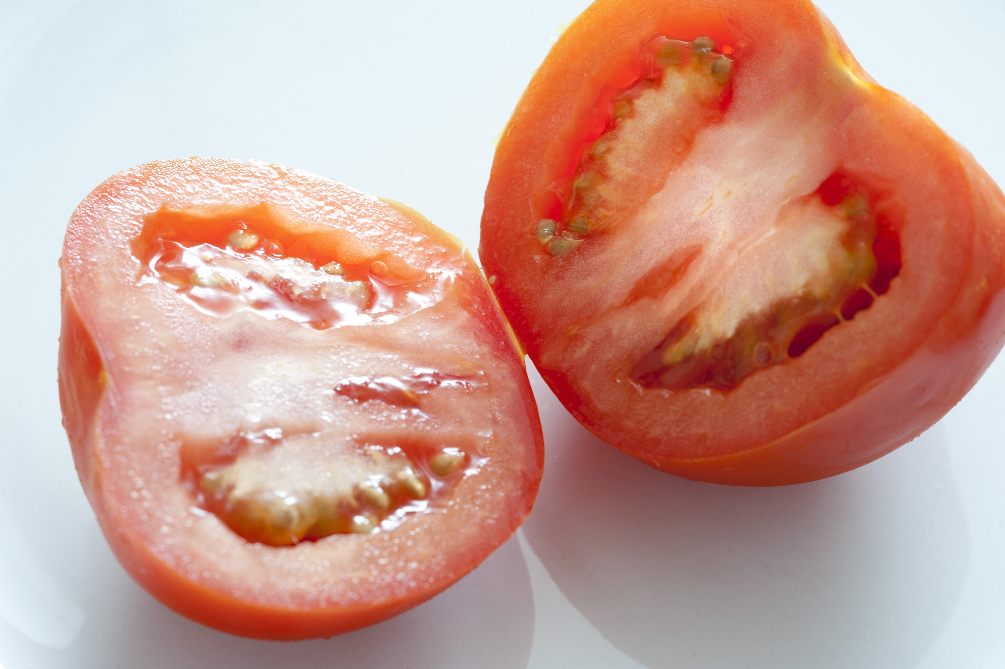 Halved fresh ripe tomato displayed to show the juicy pulp over a light grey background