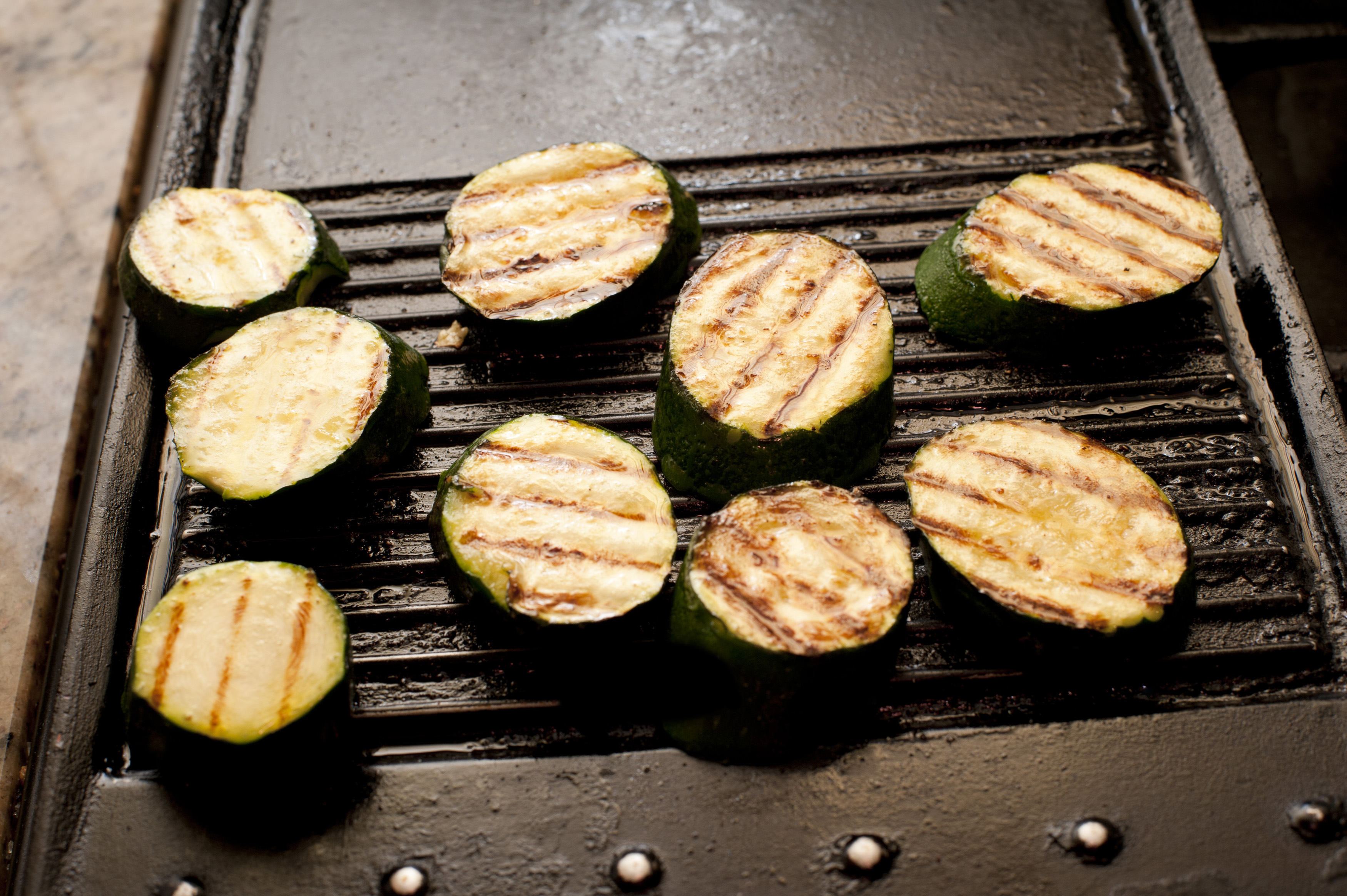 Grilled sliced brinjal or eggplant on a griddle in a kitchen preparing and cooking the vegetable for dinner