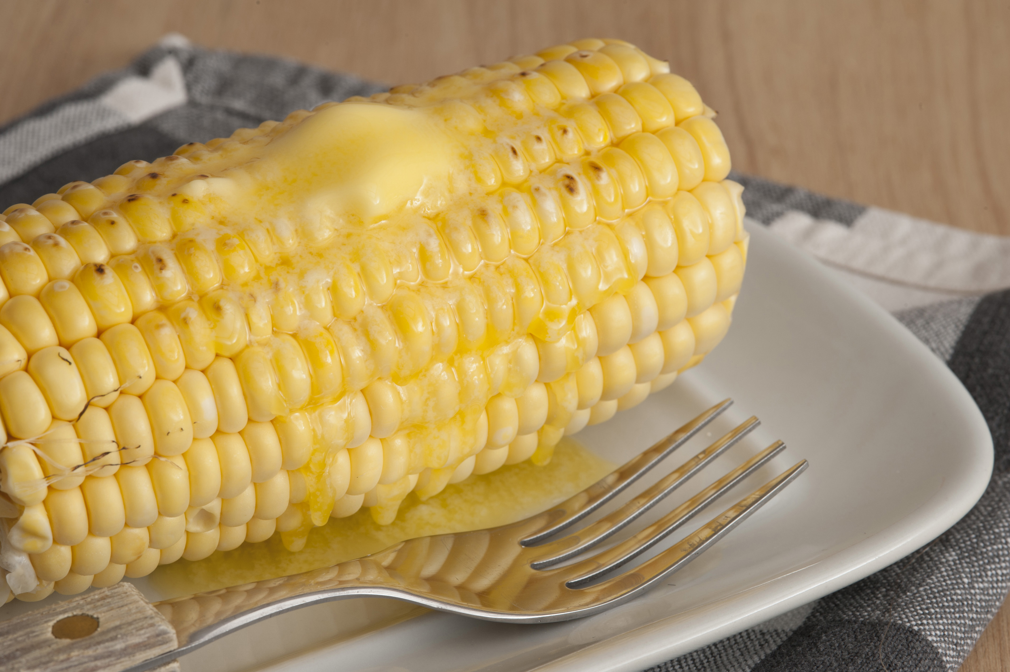 Close-up of cooked corn cob with butter on top served on white plate with fork